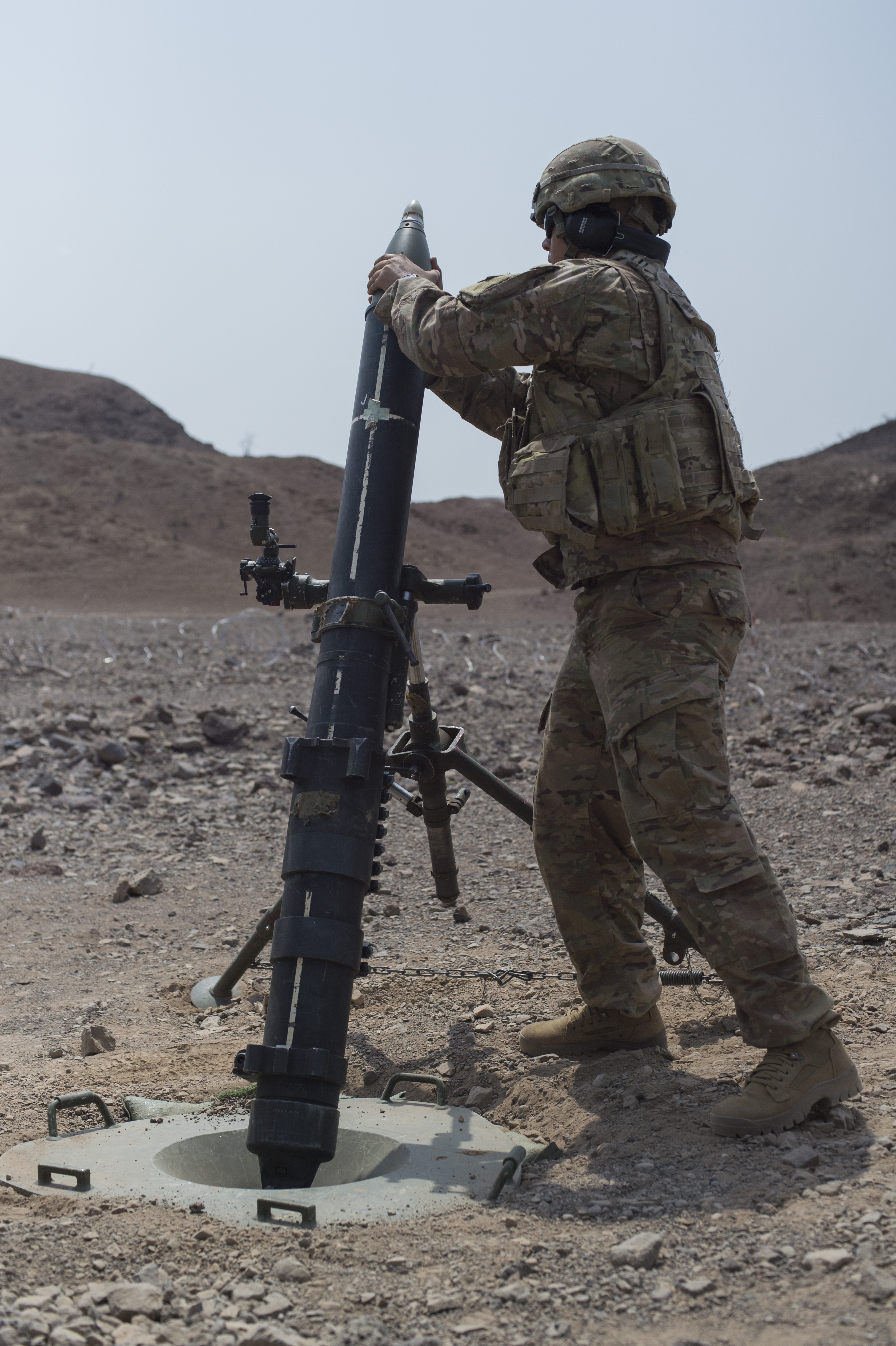 U.S. Army Spc. Alan George, 1st Battalion, 124th Infantry regiment, Bravo Company, hangs a mortar round before releasing it for deployment Aug. 8, 2016, at Arta, Djibouti. The process of 'hanging' a mortar involves holding the mortar round in the launch tube and, once the command of fire is announced, dropping the round in the tube for discharge. The 1-124, a component of Combined Joint Task Force-Horn of Africa, is deployed from Cocoa, Fla., to perform security operations in the region. (U.S. Air Force Air Force photo by Staff Sgt. Eric Summers Jr./Released)