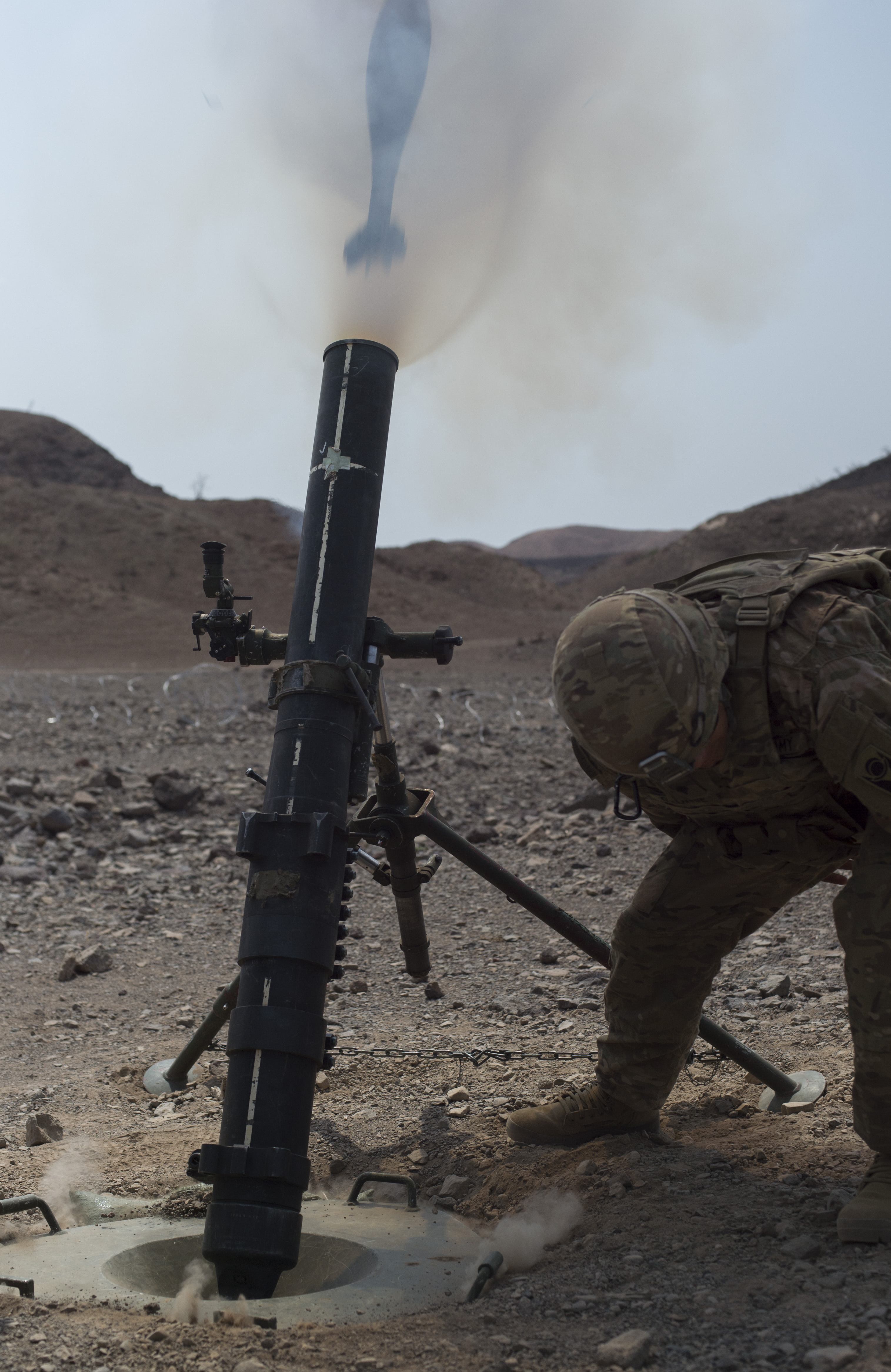 A U.S. Army Soldier from the 1st Battalion, 124th Infantry Regiment, Bravo Company fires a mortar round Aug. 8, 2016, at Arta, Djibouti. The mortar firing was part of the unit's training testing their capability to work as a team to identify a target, set-up the cannons, and accurately deploy rounds proficiently. The 1-124 is a guard unit deployed from Cocoa, Fla., to Combined Joint Task-Force Horn of Africa. (U.S. Air Force Air Force photo by Staff Sgt. Eric Summers Jr./Released)
