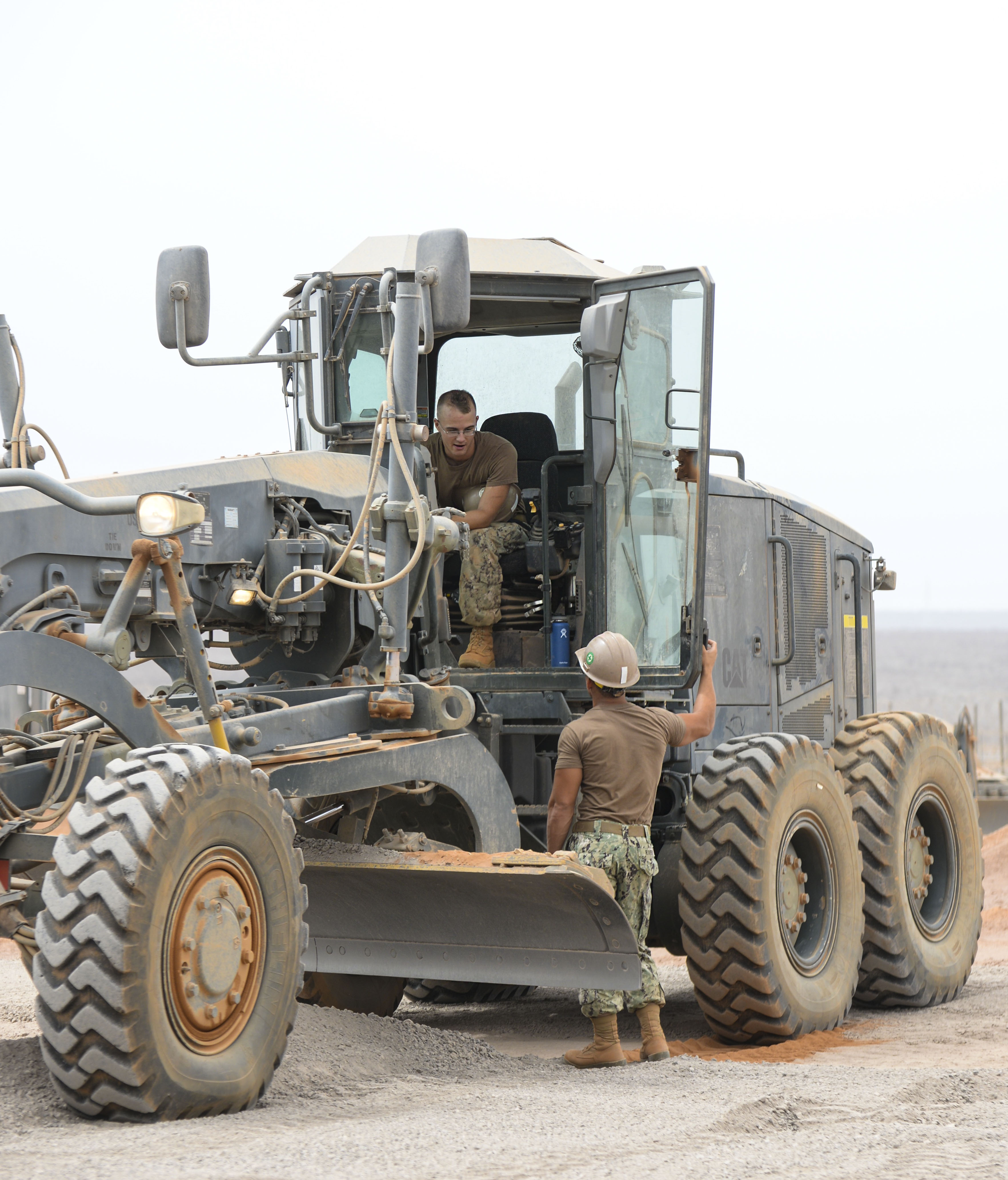 Petty Officer 3rd Class Collins Scheffer, Naval Mobile Construction Battalion 133 heavy equipment operator, left, talks to Petty Officer 2nd Class Christian Rivera, NMCB 22 heavy equipment operator, while operating a grader during construction of a parking pad at a Djibouti airfield, July 28, 2016. The grader is used to evenly spread gravel to a three-inch height during construction. (U.S. Air Force photo by Staff Sgt. Benjamin Raughton/Released)