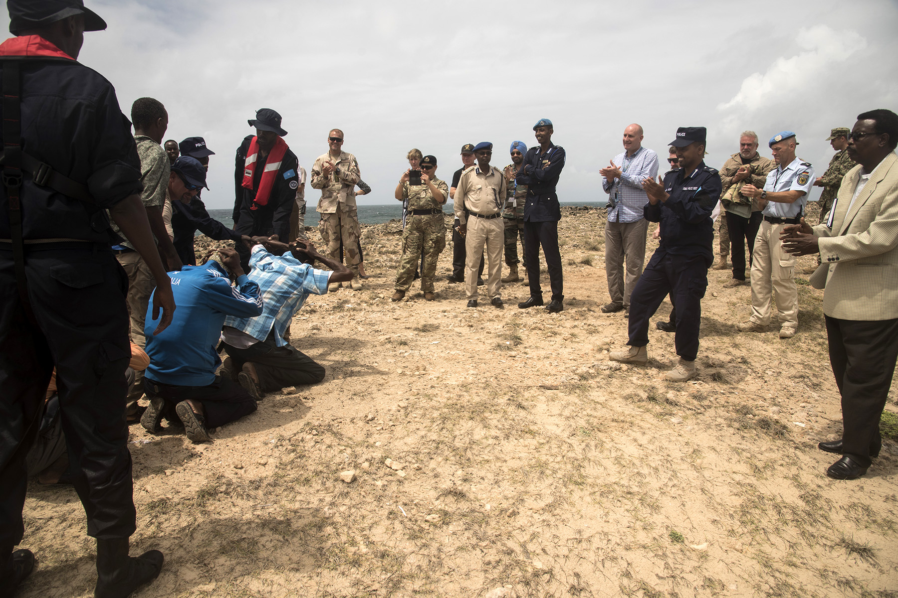 MOGADISHU, Somalia- An exercise conducted by the Somali Police Force Maritime Police Unit brings a mock captured crew to the exercise attendants in order to demonstrate the unit's capabilities with new training vessels, Aug. 25, 2016, in Mogadishu, Somalia.  Representatives from approximately seven countries working to improve security and stability in Somalia attended the exercise demonstration and brief from the United Nations Office on Drugs and Crime mentors on maritime and custodial work in Somalia. The UNODC mentors trained the maritime unit to perform interdiction operations around the coast of Somalia with their new vessels. (U.S. Air Force photo by Staff Sgt. Tiffany DeNault)