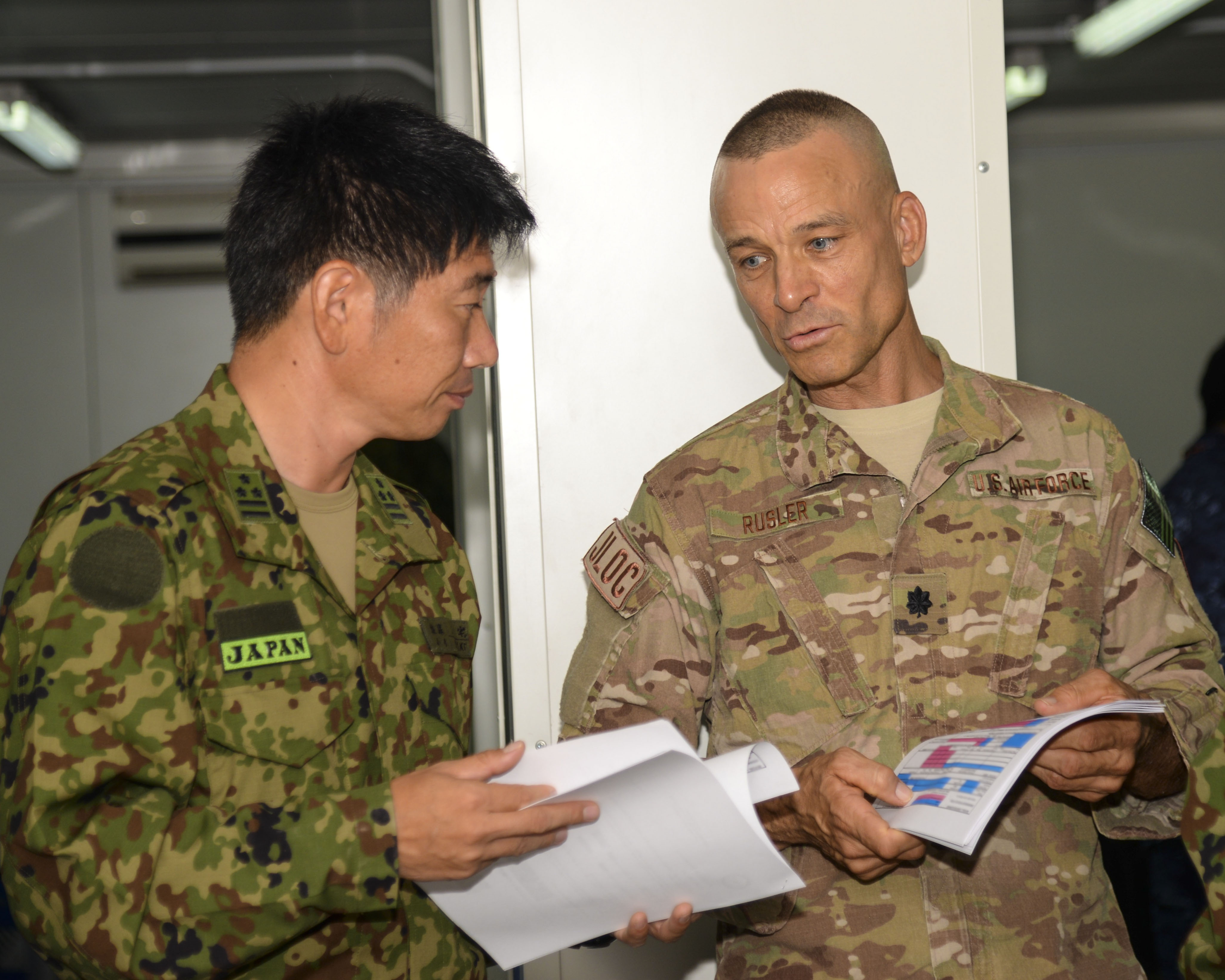 U.S. Air Force Lt. Col. Brian Rusler, Combined Joint Task Force-Horn of Africa joint logistics operations center director, speaks with Japanese service members during an exercise to discuss how they can support each other in an event involving the evacuation of Americans or Japanese from a hostile location in Africa, Aug. 28, 2016 at the Japanese base in Djibouti. During the exercise, both forces discussed route planning, logistics, equipment maintenance, how military personnel would be involved, medical support and use of air and ground transportation for evacuees. The plans also examined their strengths and weaknesses and reassessed the movement of evacuees to safety. (U.S. Air Force photo by Staff Sgt. Benjamin Raughton/Released)