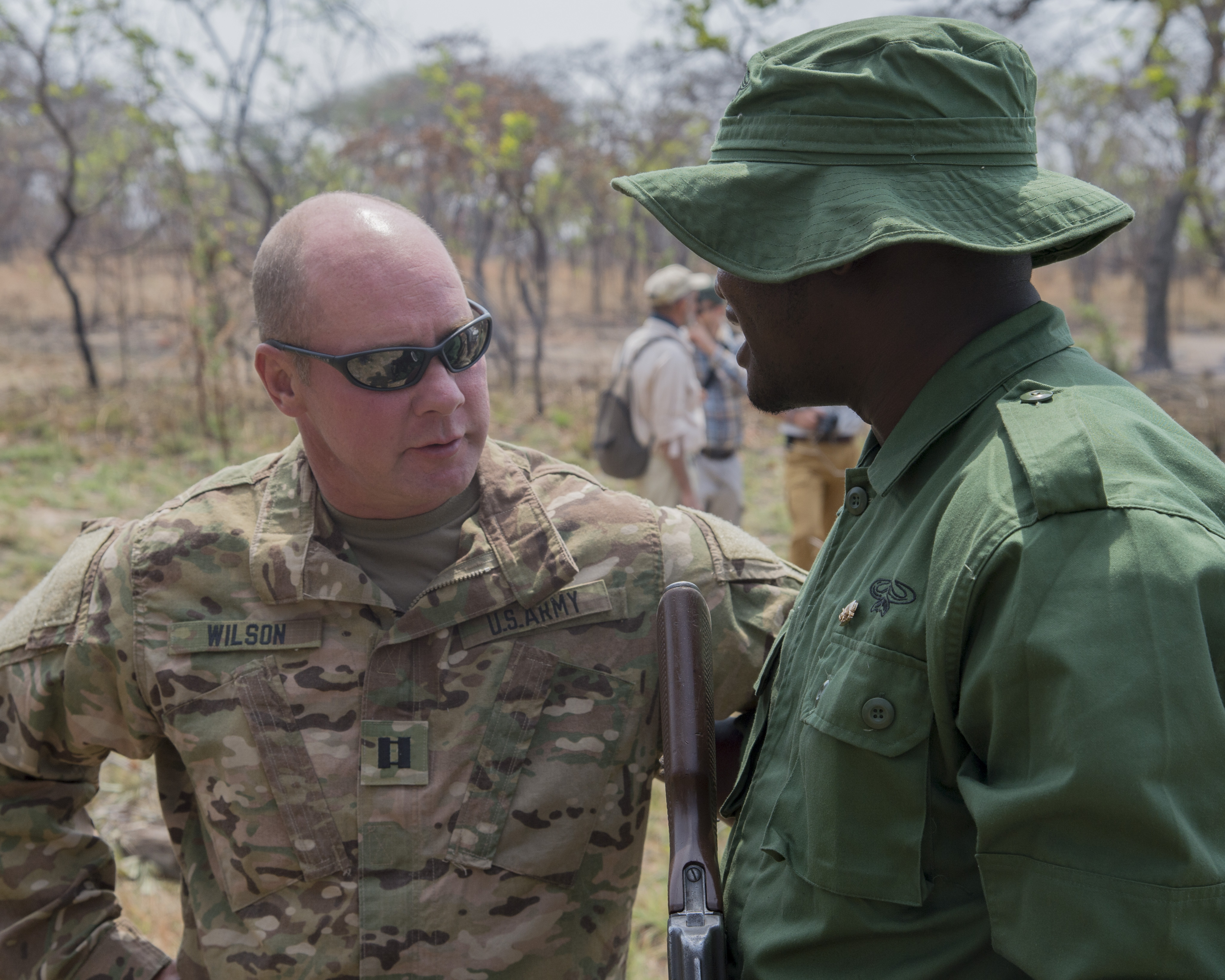 U.S. Army Capt. Michael Wilson, 403rd Civil Affairs Battalion team leader, speaks with a Tanzanian Ranger after a demonstration of capabilities Aug 24, 2016, at Rungwa Game Reserve, Tanzania. Members form the 403rd Civil Affairs Battalion, a component of Joint Task Force - Horn of Africa, and North Carolina Army National Guard, taught the rangers techniques to increase their skills in small unit tactics, first aid, gathering intelligence and other field crafts. The soldiers were training the rangers in how to combat poachers on the reserve.  Poaching and trafficking in wildlife has become a source of revenue for violent extremist organizations on the continent. (U.S. Air Force photo by Staff Sgt. Eric Summers Jr./Released)