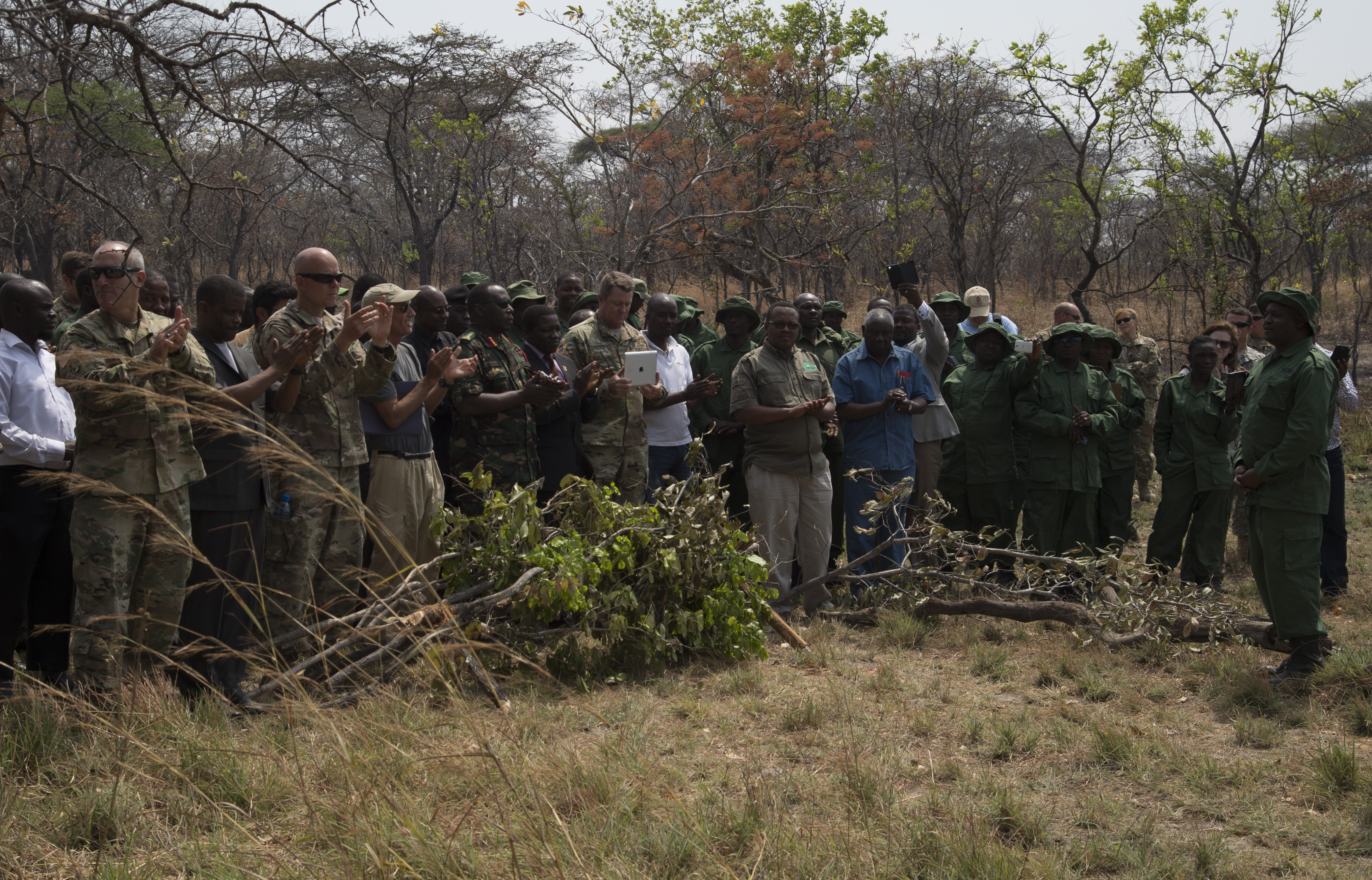 Audience members from the Ministry of Natural Resources and Tourism, Combined Joint Task Force - Horn of Africa, U.S. Embassy Tanzania and North Carolina Army National Guard clap for Tanzania park and game reserve rangers following a demonstration August 24, 2016, at Rungwa Game Reserve, Tanzania. Rangers recently trained with members of the 403rd Civil Affairs Battalion, a component of Combined Joint Task Force - Horn of Africa, and North Carolina Army National Guard to learn techniques to track and capture poachers. (U.S. Air Force photos by Staff Sgt. Eric Summers Jr.)