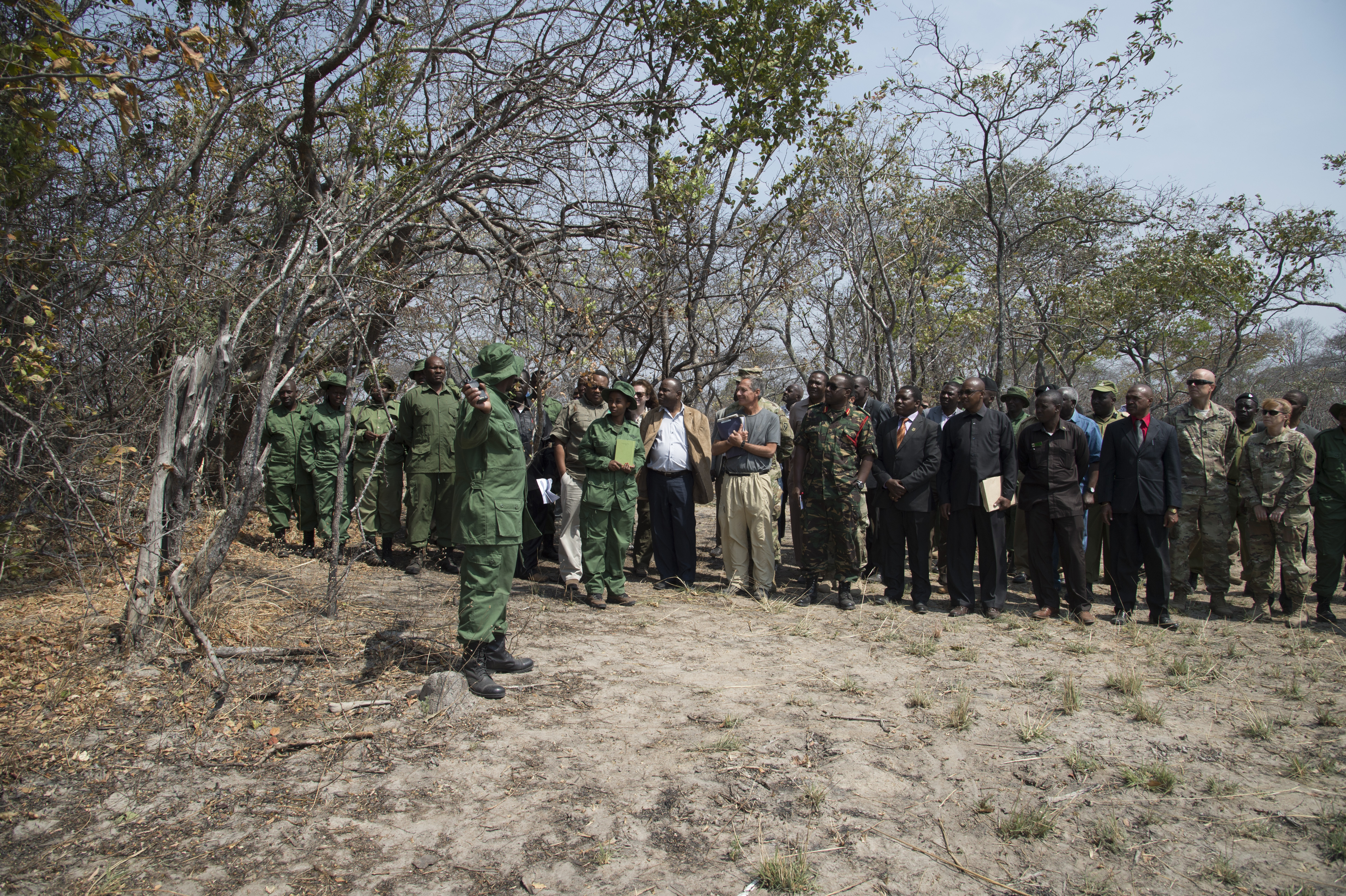 Spectators from the Ministry of Natural Resources and Tourism, Combined Joint Task Force - Horn of Africa, U.S. Embassy Tanzania and North Carolina Army National Guard listen to a briefing before witnessing the raid of a simulated poacher camp August 24, 2016, at the Rungwa Game Reserve, Tanzania. Tanzania rangers recently trained with members of the 403rd Civil Affairs Battalion, a component of Combined Joint Task Force - Horn of Africa, and North Carolina Army National Guard to learn techniques to track and capture poachers. The training is part of the Tanzanian government and U.S. Embassy's plan to reduce wildlife poaching in the country. (U.S. Air Force photo by Staff Sgt. Eric Summers Jr.)