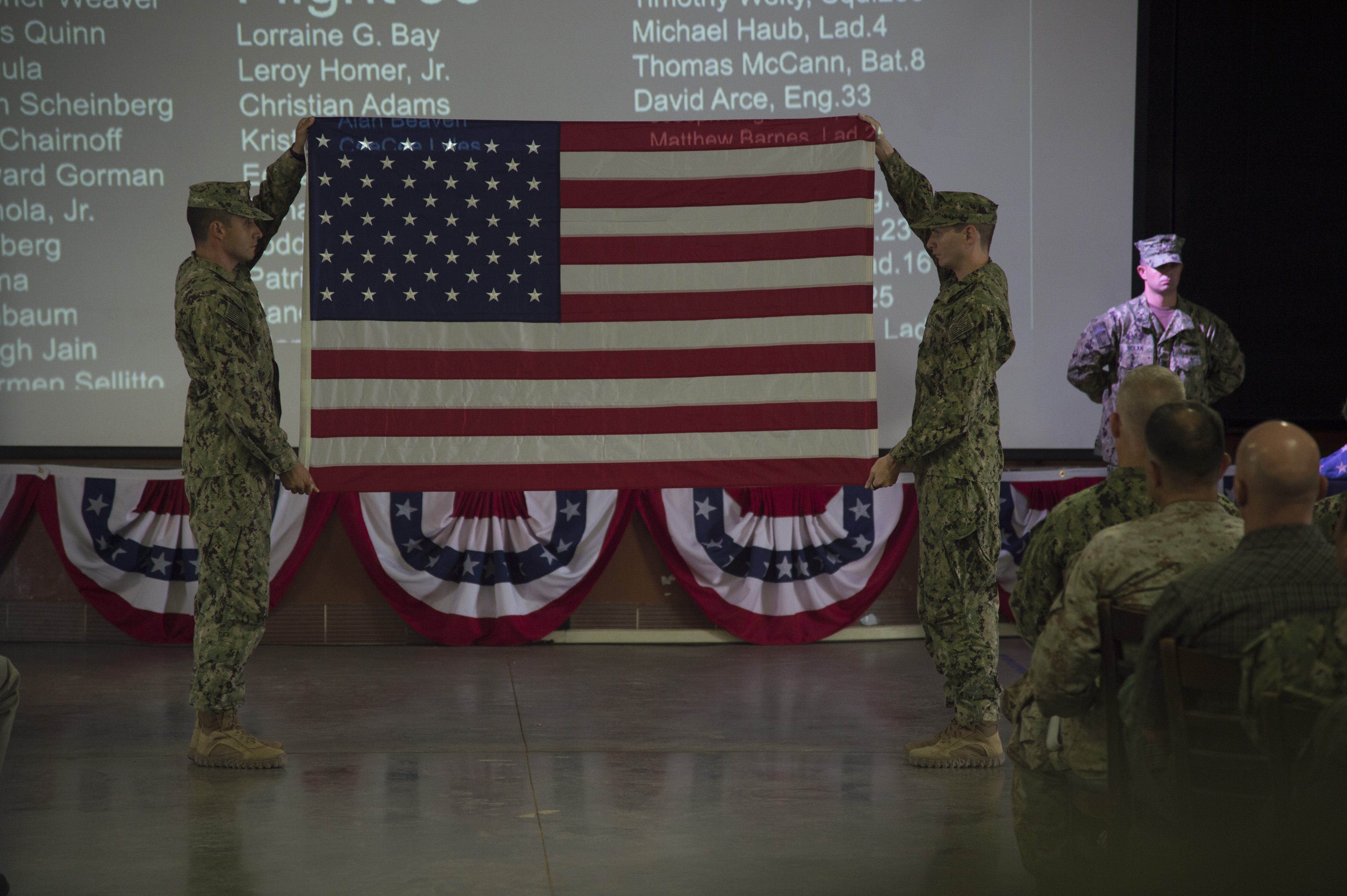 U.S. Navy Sailors display an American flag to the crowd before folding and giving it to U.S. Army Maj. Eric Torrado during a 9/11 remembrance ceremony held Sept. 11, 2016, at Camp Lemonnier, Djibouti. Torrado is part of the New York Army National Guard and works for the New York City Police Department when he is not performing military duties. The ceremony was organized and conducted by Fiscal Year 2017 Chief Petty Officer selectees from Camp Lemonnier and Combined Joint Task Force - Horn of Africa.  (U.S. Air Force photo by Staff Sgt. Eric Summers Jr.)