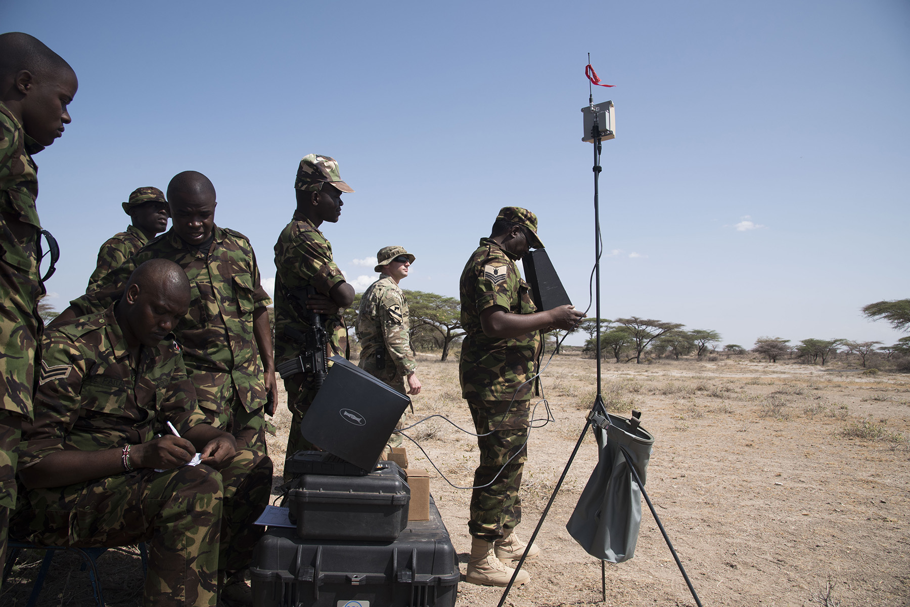 U.S. Army Staff Sgt. Charles Wirks, 1st Battalion, 124th Infantry Regiment and Raven master trainer, and members of the Kenya Defense Forces Military Intelligence Battalion, use an imagery system to fly the AeroVironment RQ-11 Raven, an unmanned aerial vehicle, Sept. 13, 2016, at a Kenyan training facility. U.S. Army Soldiers from the 1/124th Inf. Rgt., assigned to Combined Joint Task Force-Horn of Africa, provided basic training on assembly, disassembly, repair, and preventative maintenance in regard to basic mission planning and advanced flight plans for the Raven. (U.S. Air Force photo by Staff Sgt. Tiffany DeNault)