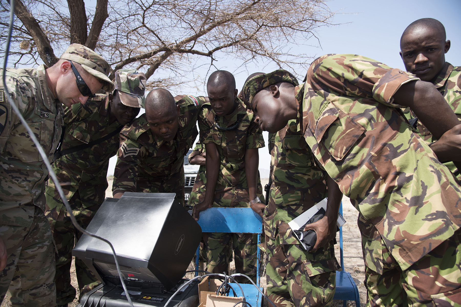 U.S. Army Staff Sgt. Charles Wirks, 1st Battalion, 124th Infantry Regiment and Raven master trainer, and members of the Kenya Defense Forces Military Intelligence Battalion set up a computer system in preparation to fly the AeroVironment RQ-11 Raven, an unmanned aerial vehicle, Sept. 13, 2016, at a Kenyan training facility. U.S. Army Soldiers from the 1/124th Inf. Rgt., assigned to Combined Joint Task Force-Horn of Africa, provided basic training on assembly, disassembly, repair, and preventative maintenance in regard to basic mission planning and advanced flight plans for the Raven. (U.S. Air Force photo by Staff Sgt. Tiffany DeNault)