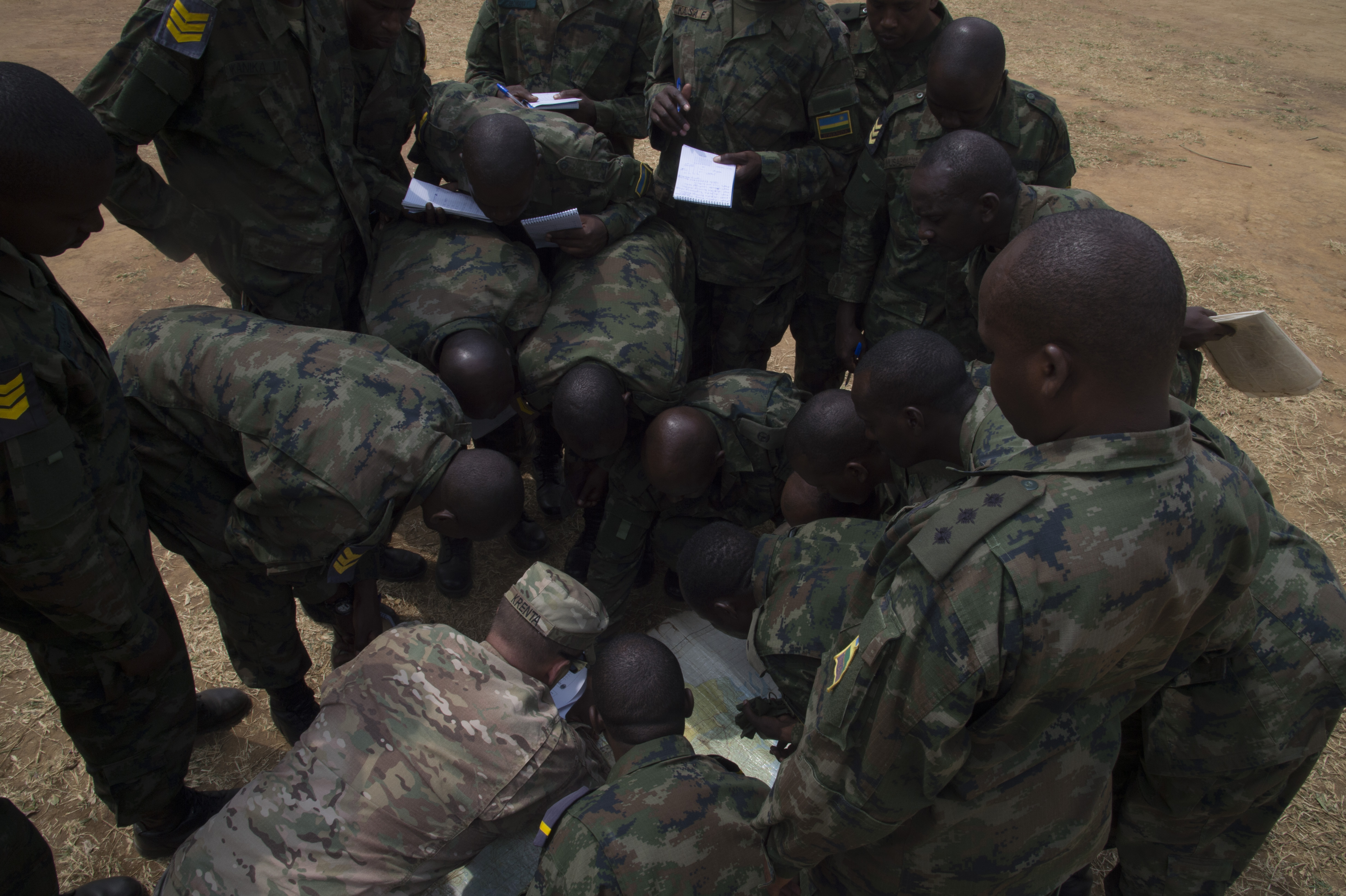U.S. Army 1st Sgt. Jason Krenta, 1st Battalion, 124th Infantry Regiment, shows Rwanda Defense Force soldiers how to use a protractor and a map to plot grid coordinates Sept. 8, 2016, at the Rwanda Military Academy, Rwanda. Krenta, deployed to Combined Joint Task Force - Horn of Africa from the Florida Army National Guard, was part of a two-man team to observe and provide advice during a Rwandan noncommissioned officer leadership course. (U.S. Air Force photo by Staff Sgt. Eric Summers Jr.)