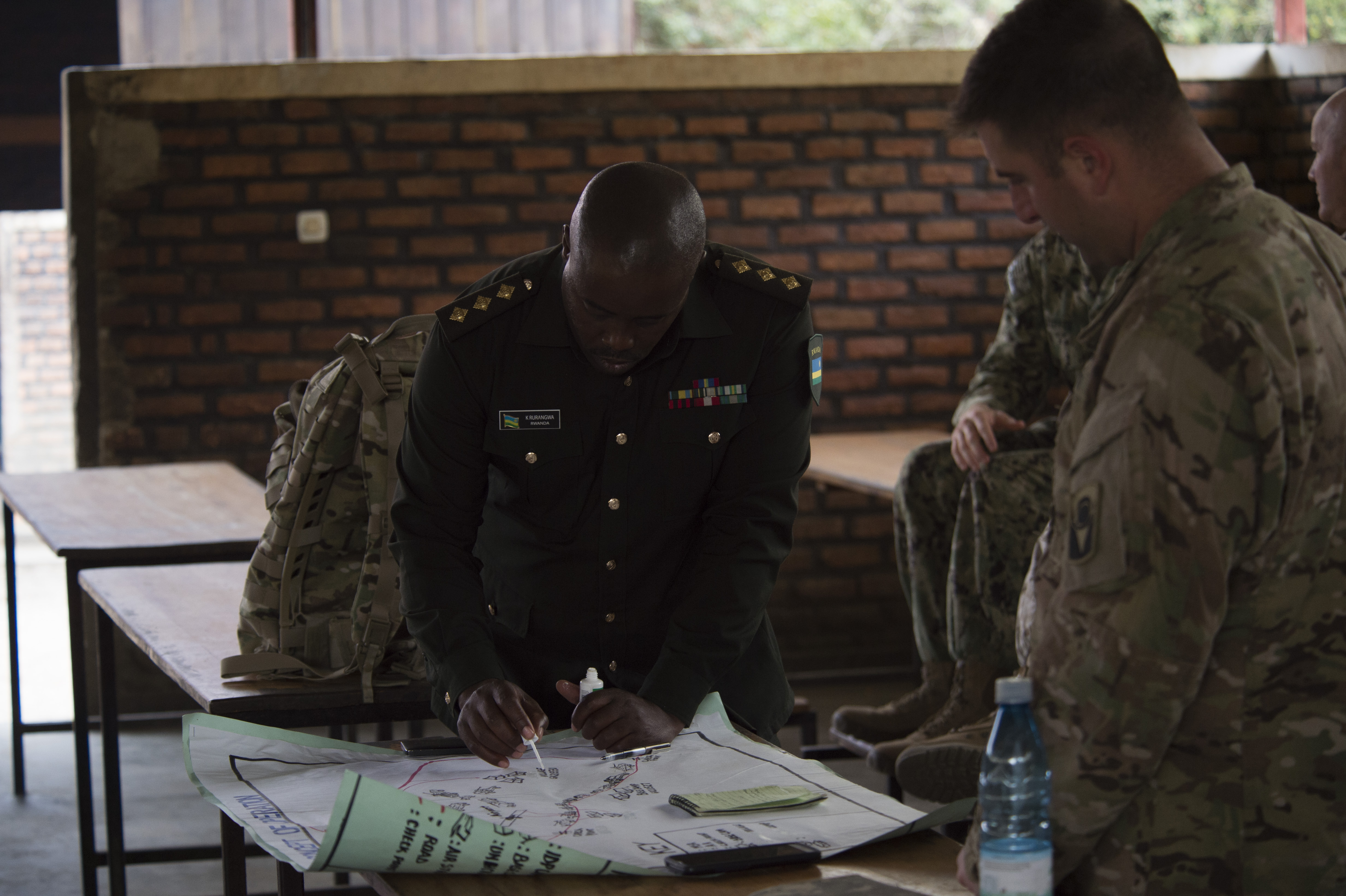 A Rwanda Defense Force captain and U.S. Army 1st Sgt. Jason Krenta, 1st Battalion, 124th Infantry Regiment, review and make changes to a map in preparation for practical land navigation training Sept. 8, 2016, at the Rwanda Military Academy, Rwanda. Krenta, deployed to Combined Joint Task Force - Horn of Africa from the Florida Army National Guard, was part of a two-man team to observe and provide advice during a Rwandan NCO leadership course. (U.S. Air Force photo by Staff Sgt. Eric Summers Jr.)