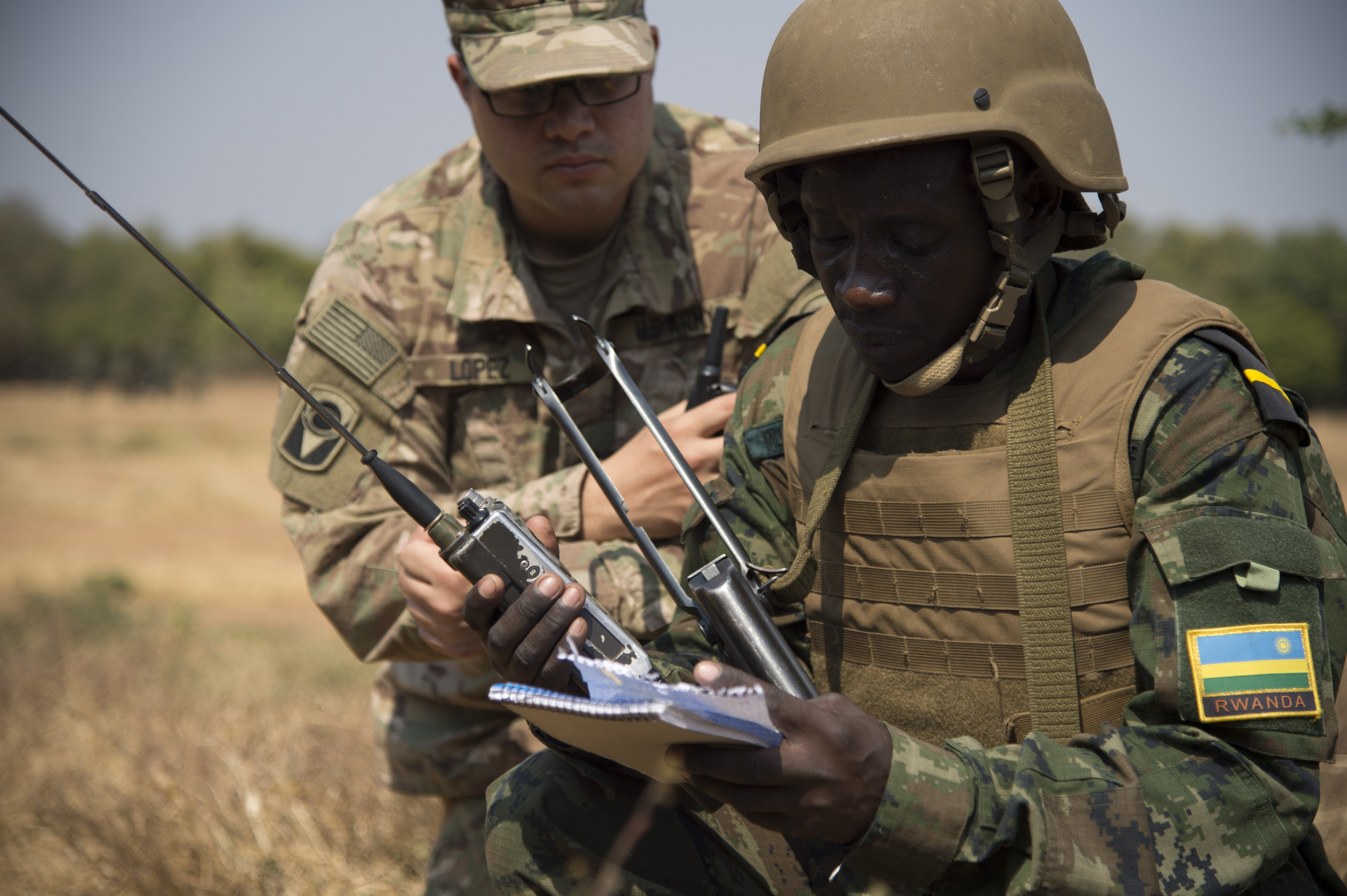 A Rwanda Defense Force soldier calls in a 9-line report to request a medical evacuation, while Army Sgt. Jonathan Lopez, 1st Battalion, 124th Infantry Regiment medic, observes during a medical exercise Sept. 9, 2016, at the Rwanda Military Academy, Rwanda. The exercise, part of a two-week medical course, tested the RDF soldiers' abilities to apply techniques of care under fire and other battlefield medical tactics. U.S. Army Soldiers from the 1st Battalion, 124th Infantry Regiment, assigned to Combined Joint Task Force-Horn of Africa, instructed the course. (U.S. Air Force photo by Staff Sgt. Eric Summers Jr.)