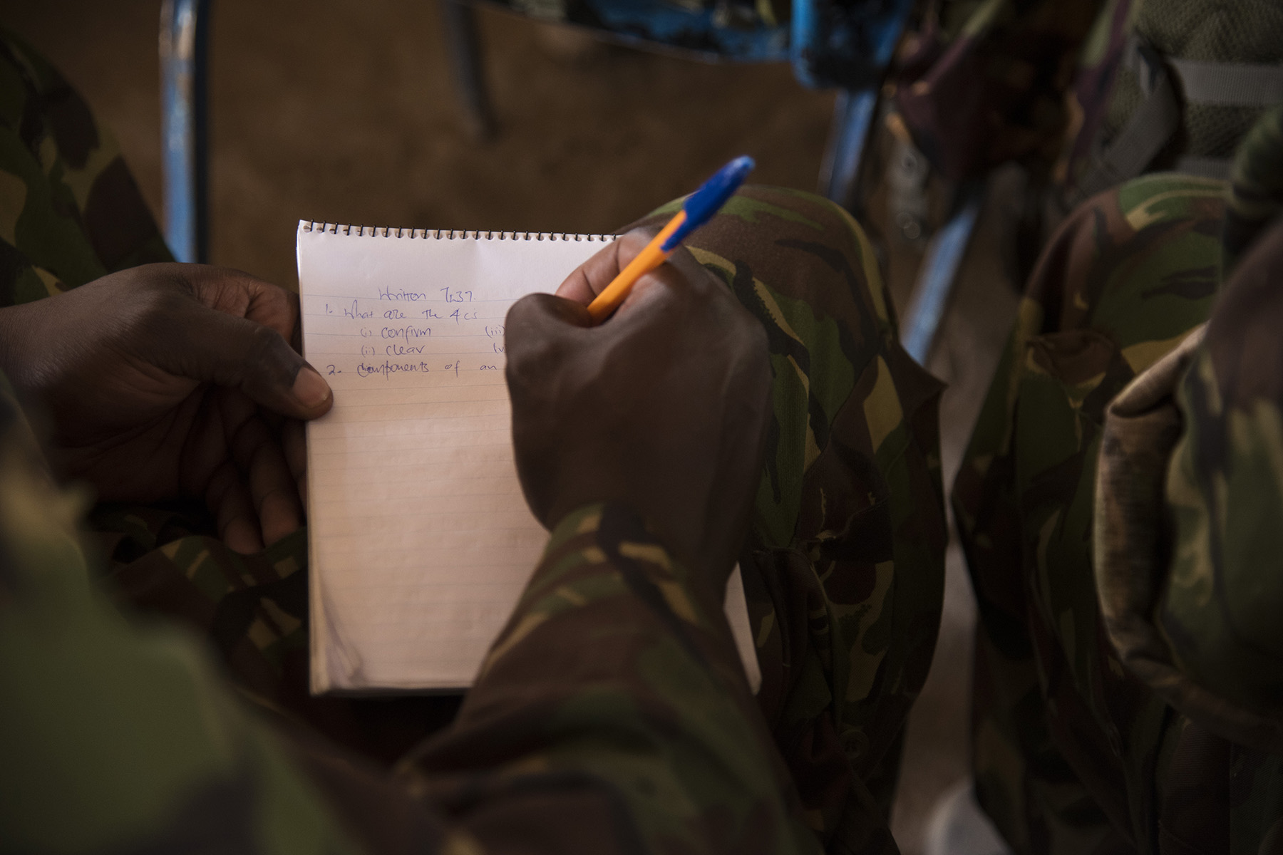 KENYA- Kenya Defense Forces combat engineer soldiers and officers complete a written test at the end of their second week of class during Deliberate Kindle 2016, Sept. 16, at a training center in Kenya. U.S. Navy Task Force Sparta explosive ordnance disposal technicians and a dive independent duty corpsman, assigned to Combined Joint Task Force-Horn of Africa, provided counter-improvised explosive device, tactical combat medical care, and train-the-trainer skills to approximately 53 KDF soldiers and officers in preparation the KDF's deployment with the African Union Mission in Somalia. (U.S. Air Force photo by Staff Sgt. Tiffany DeNault)