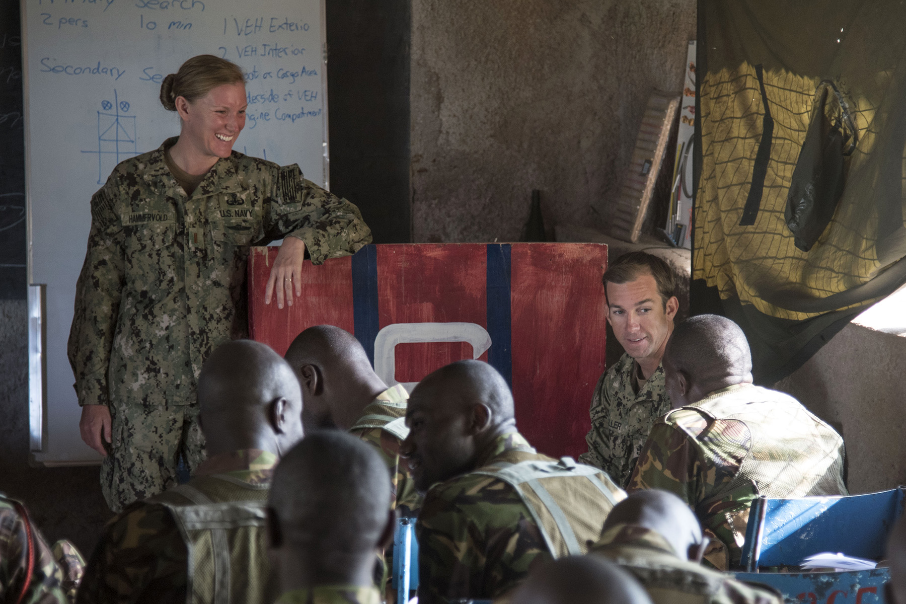 KENYA – U.S. Navy Ensign Christina Hammervold and Chief Petty Officer Ryan Waller, Task Force Sparta, speak with Kenya Defense Forces Warrant Officer Athumani, a squadron sergeant major, before resuming the medical portion of Deliberate Kindle 2016, Sept. 13, at a training center in Kenya. U.S. Navy explosive ordnance disposal technicians and a dive independent duty corpsman provided counter-improvised explosive device, tactical combat medical care, and train-the-trainer skills to approximately 53 KDF soldiers and officers in preparation the KDF's deployment with the African Union Mission in Somalia. (U.S. Air Force photo by Staff Sgt. Tiffany DeNault)