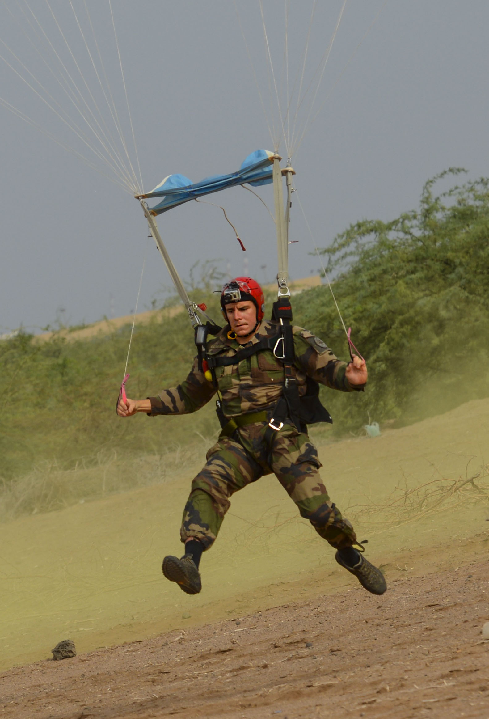 A French airborne soldier lands safely on the ground during a high altitude low opening jump in celebration of St. Michel's Day in Djibouti, Sept. 29, 2016. The celebration was in honor of St. Michel, the patron saint of paratroopers, and included a celebratory mass and American jumpers being awarded French jump wings. (U.S. Air Force photo by Staff Sgt. Benjamin Raughton)