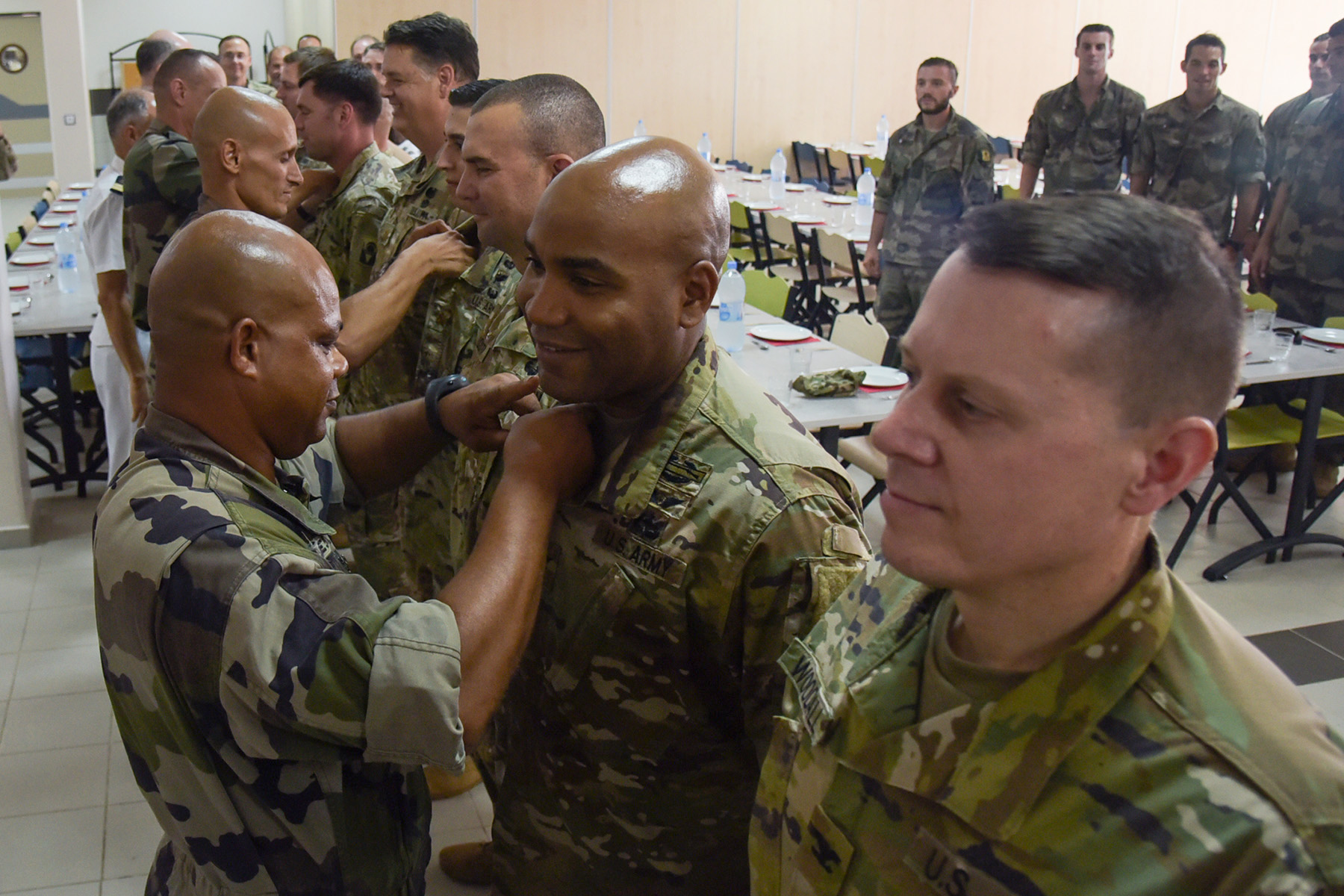 DJIBOUTI- French airborne forces pin jump wings on U.S. Army Soldiers for completing static line and high altitude low opening (HALO) jumps commemorating St. Michel, the patron saint of paratroopers, Sept. 29, 2016, at the French air base in Djibouti City, Djibouti. U.S., French and Djiboutian airborne forces began the St. Michel celebration with a static line and HALO jump at a designated drop zone, followed by a church mass and a ceremony where several U.S. airborne forces were awarded French jump wings. (U.S. Air Force photo by Staff Sgt. Tiffany DeNault)