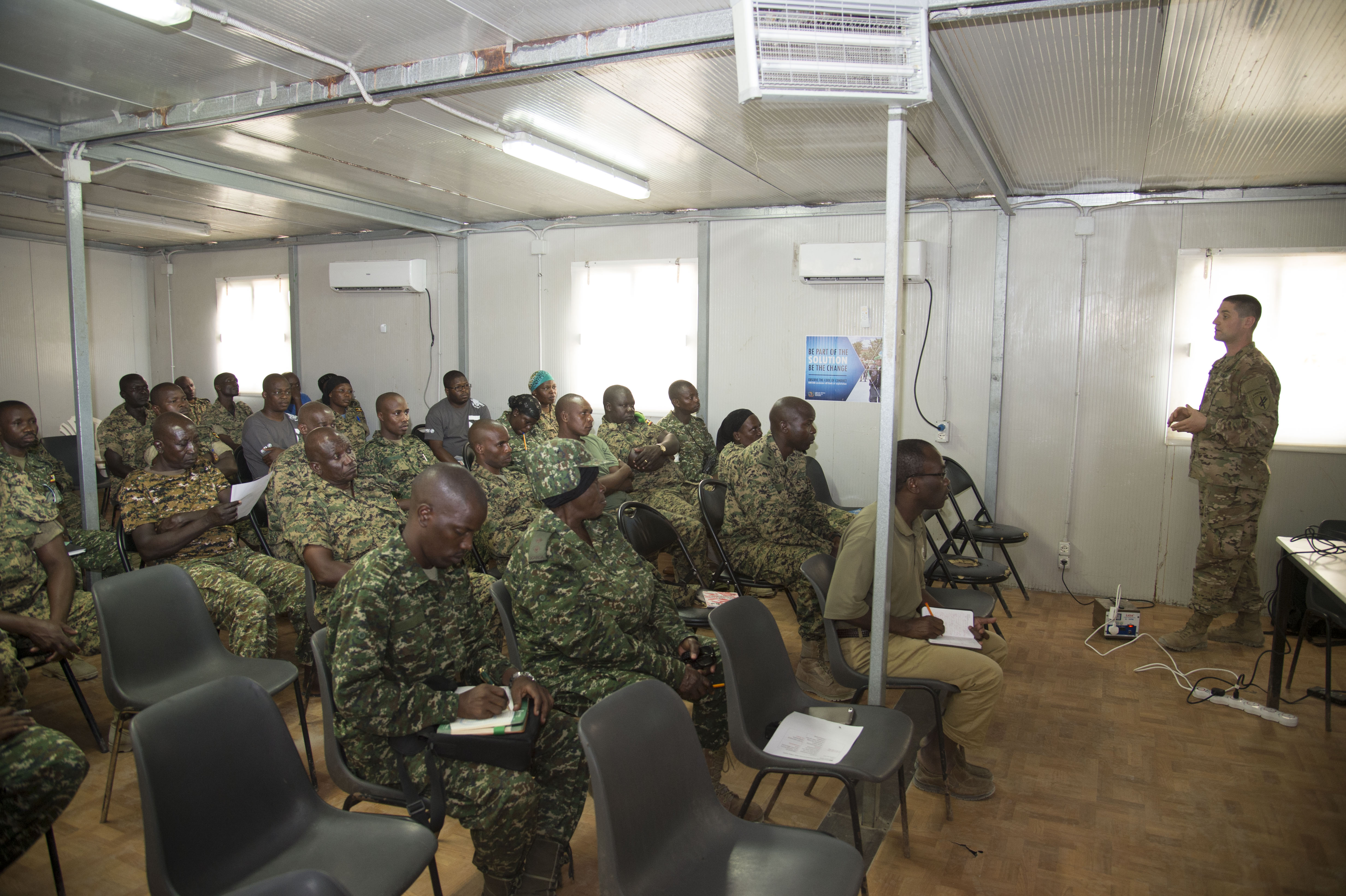 Members of the Uganda People's Defense Force (UPDF) listen to U.S. Army Staff Sgt. Matthew Glaberman, Charlie Company, 411th Civil Affairs Battalion operations sergeant, as he speaks about ways to prepare for combat stress before a deployment Oct 10, 2016, at Mogadishu, Somalia. The UPDF is deployed in support of the African Union Mission to Somalia to combat extremist terrorists in the region and restore stability. (U.S. Air Force photo by Staff Sgt. Eric Summers Jr.)
