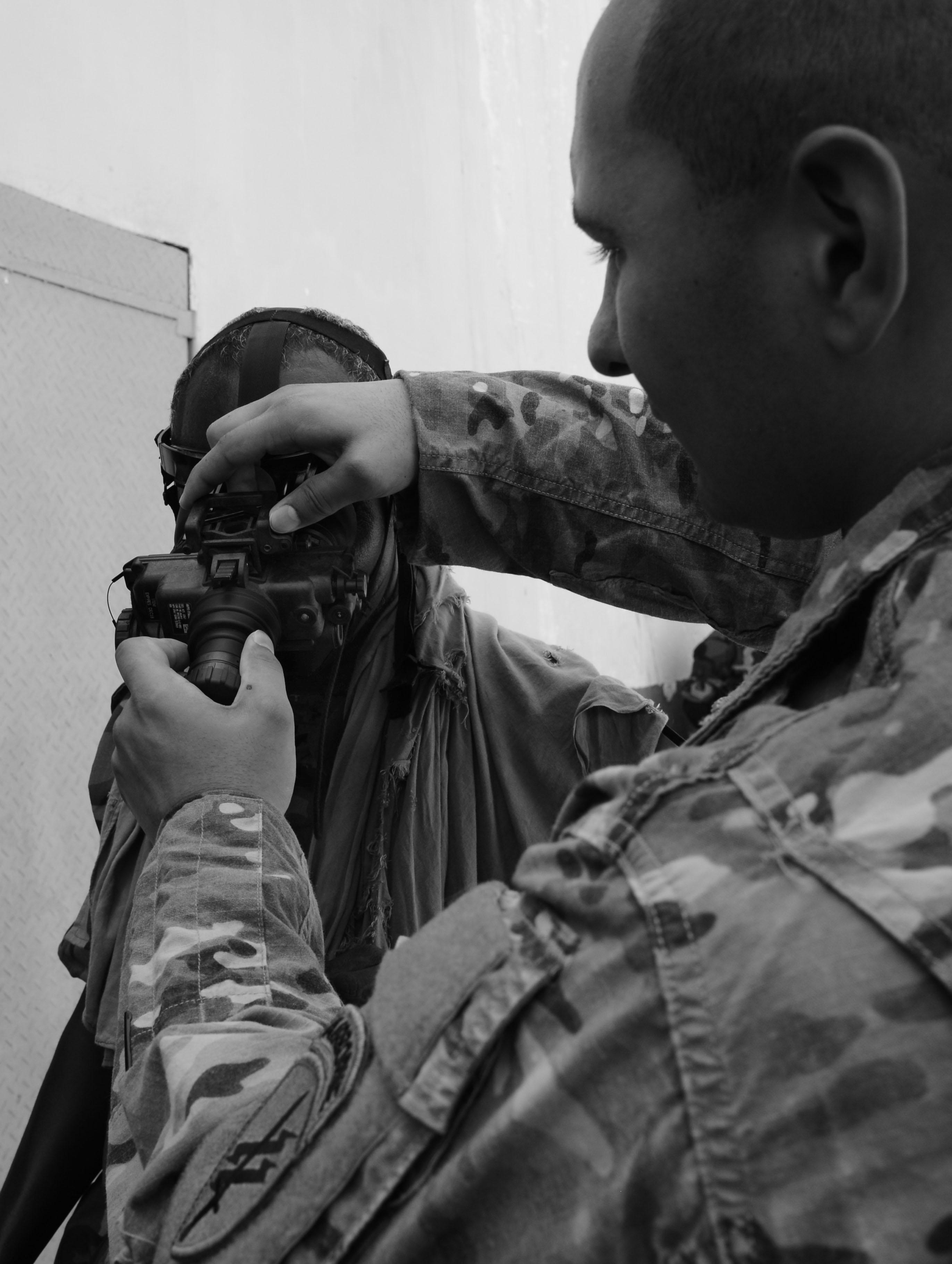 U.S. Army Spc. Christian Kelly, Charlie Company, 411th Civil Affairs Battalion team member, adjusts a Djiboutian soldier's night vision goggles head mount in Djibouti City, Oct. 10, 2016. Soldiers worked in small teams to navigate obstacles in a dark room to find a designated object and bring it back outside the building during the NVG exercise. (U.S. Air Force photo by Staff Sgt. Benjamin Raughton)