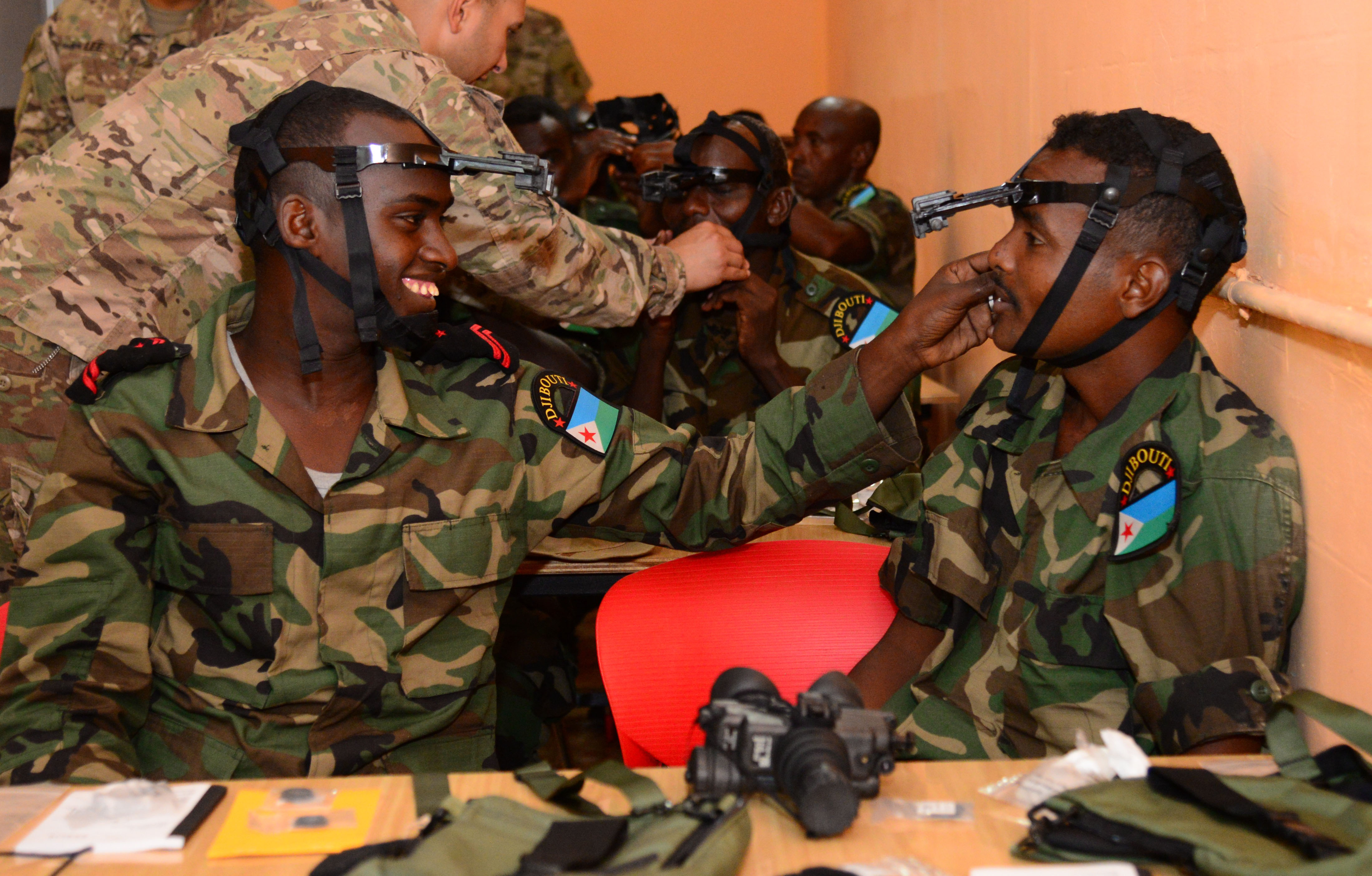 Djiboutian Army Cpl. Yosin, left, helps a fellow soldier, Mohamed, adjust his night vision goggle headmount during a night-vision goggle training course in Djibouti City, Djibouti, Oct. 10, 2016. Soldiers were tested on how quickly they could don their NVG gear during the class. (U.S. Air Force photo by Staff Sgt. Benjamin Raughton)