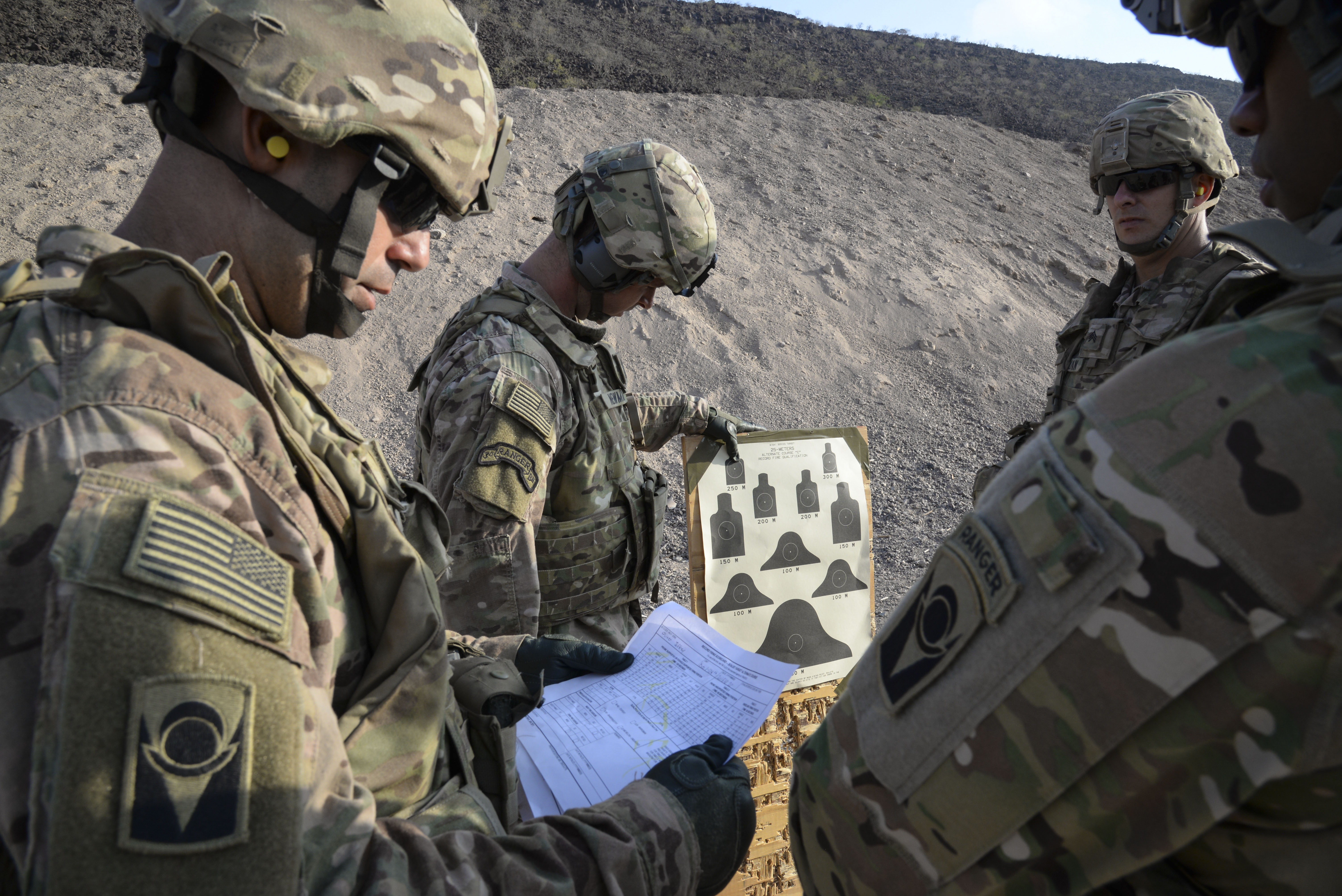 U.S. Army soldiers of Delta Company, 1st Battalion, 124th Infantry Regiment, review their shooting performance after a rifle qualification exercise in Arta, Djibouti, Oct. 20, 2016. The training began with a routine rifle qualification, followed by an exercise designed to teach soldiers how to handle a situation when their vehicle takes direct enemy fire in a combat zone. (U.S. Air Force photo by Staff Sgt. Benjamin Raughton)