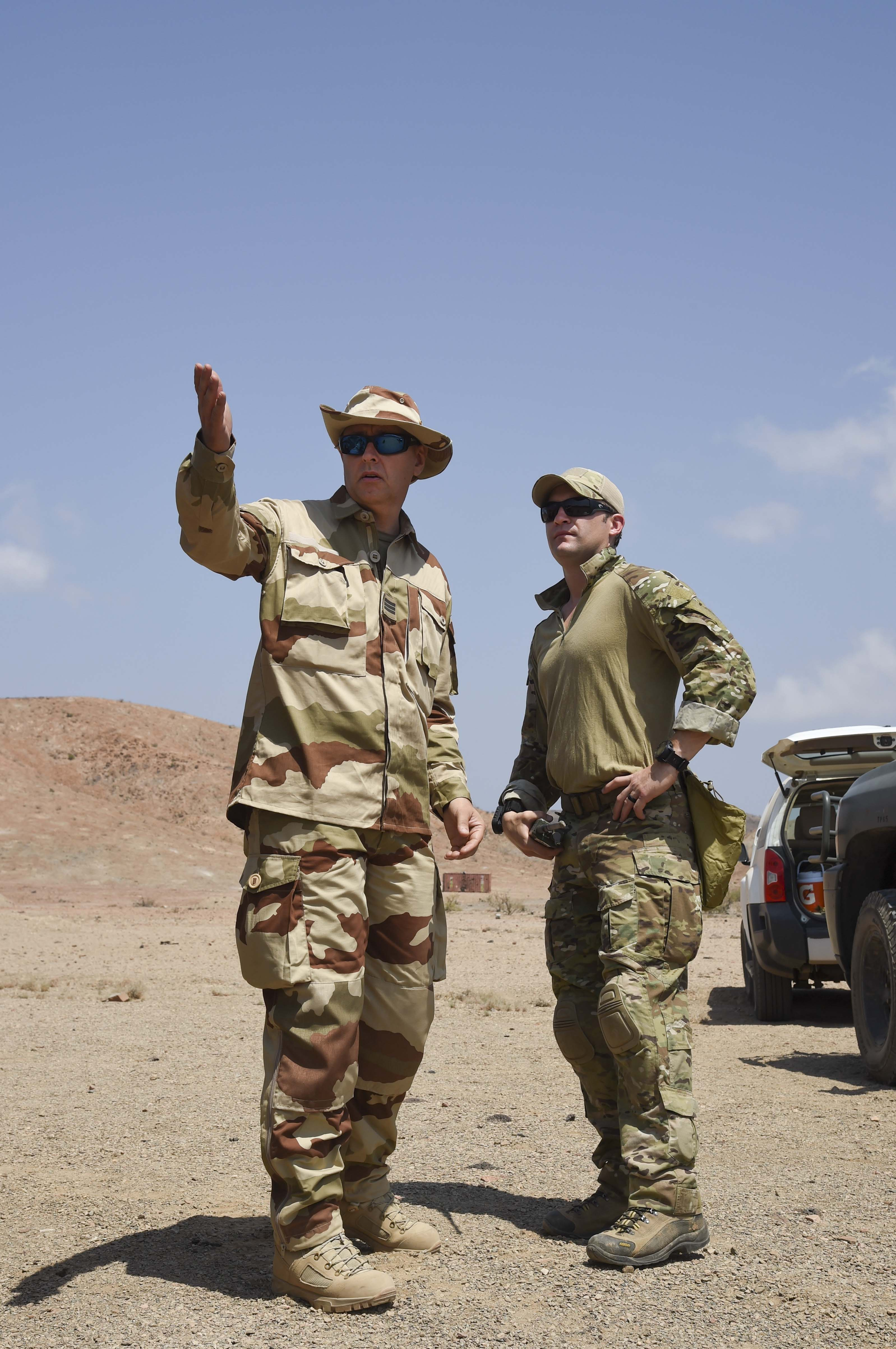 French Capt. Philippe, Explosive Ordnance Disposal (EOD), communicates with U.S. Navy Chief Petty Officer Adam Bartch, EOD Mobile Unit 6, Task Force Sparta, range safety officer, during range clearing operations on a range, Oct. 22, 2016, in Djibouti. During this operation, Navy and French EOD personnel worked bilaterally to safely clear their respective areas of unexploded ordnance. (U.S. Air Force photo by Staff Sgt. Penny Snoozy)