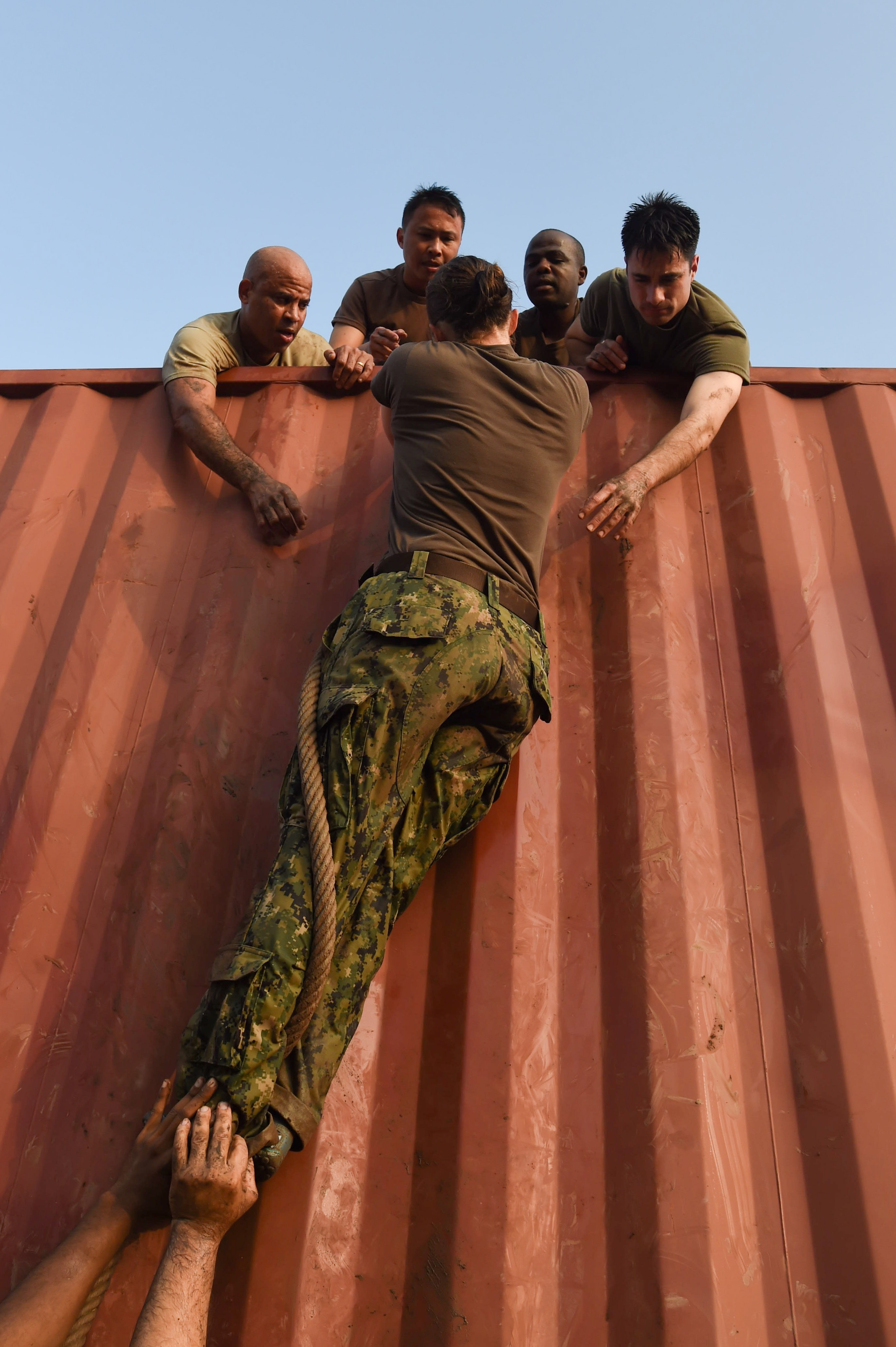 U.S. Navy Lt. Cmdr. Brighid Clark, Combined Joint Task Force-Horn of Africa Civil Affairs, pulls herself to the top of a rope climb with assistance from her team during a mud run hosted by the French military, Nov. 6, 2016, in Djibouti, Djibouti. The event allowed coalition forces from French, Japanese, and American teams to interact and build camaraderie while navigating a five kilometer course. The French 5th Marine Regiment team took first place. (U.S. Air Force photo by Staff Sgt. Penny Snoozy)