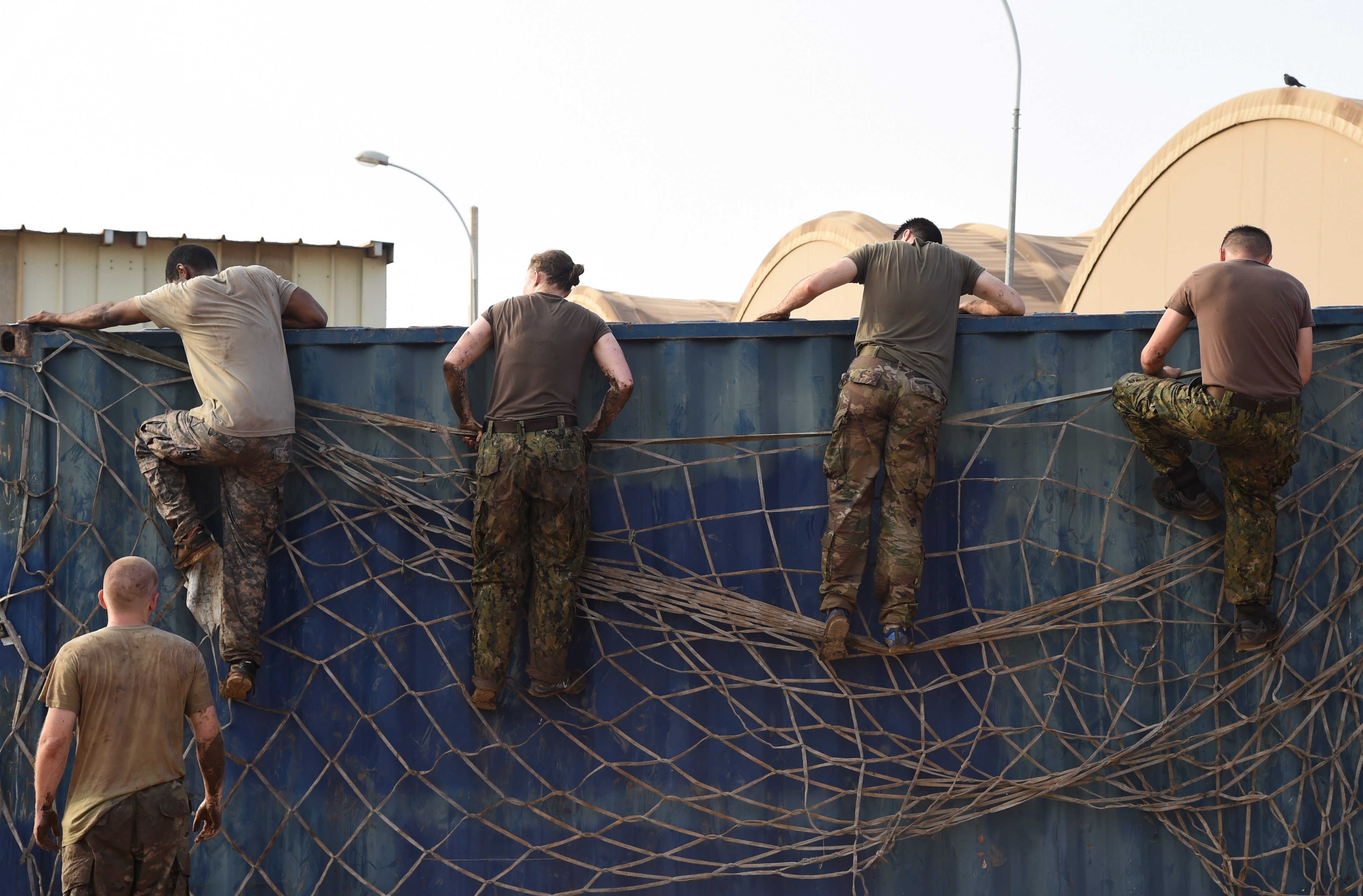Service members from Combined Joint Task Force-Horn of Africa Civil Affairs climb over an obstacle during a mud run hosted by the French military, Nov. 6, 2016, in Djibouti, Djibouti. The event allowed coalition forces from French, Japanese, and American teams to interact and build camaraderie while navigating a five kilometer course. The French 5th Marine Regiment team took first place. (U.S. Air Force photo by Staff Sgt. Penny Snoozy)