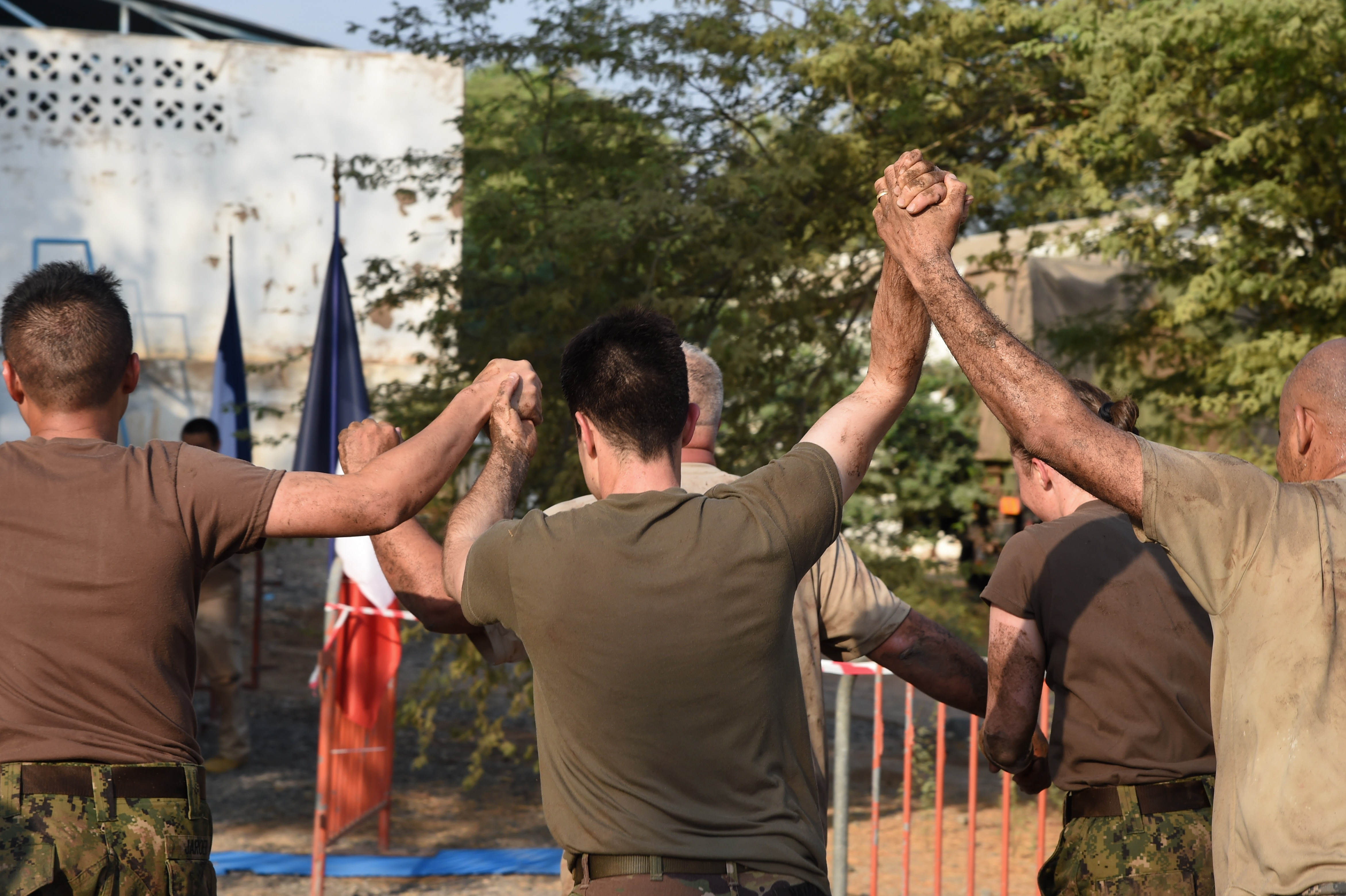 Service members from Combined Joint Task Force-Horn of Africa Civil Affairs complete the final stretch of the course during a mud run hosted by the French military, Nov. 6, 2016, in Djibouti, Djibouti. The event allowed coalition forces from French, Japanese, and American teams to interact and build camaraderie while navigating a five kilometer course. The French 5th Marine Regiment team took first place. (U.S. Air Force photo by Staff Sgt. Penny Snoozy)