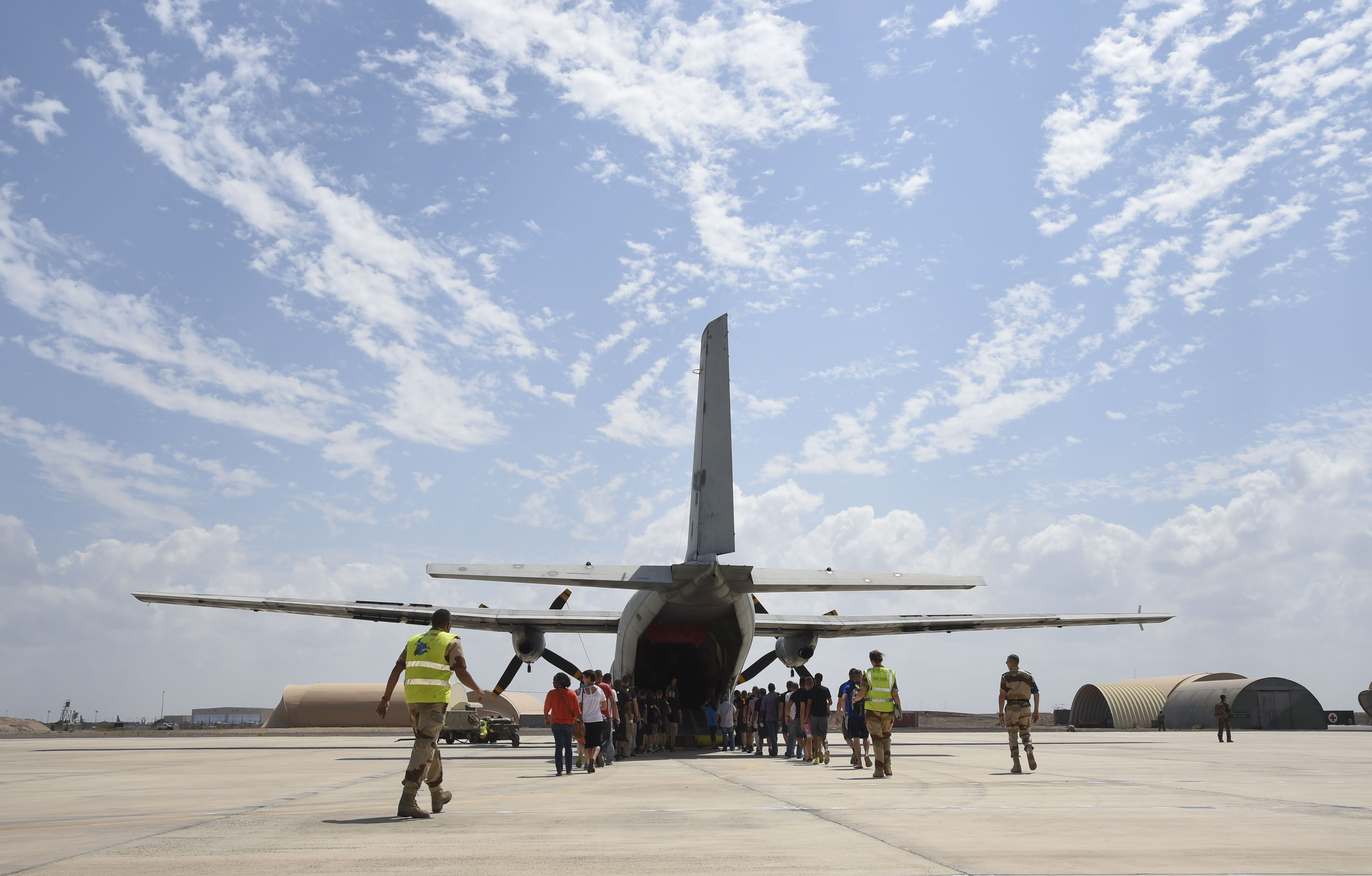 U.S. service members assigned to Combined Joint Task Force-Horn of Africa and volunteers proceed to an aircraft during a non-combatant evacuation exercise (NEO) at the French Marine 5th Regiment, Nov. 16, 2016, in Djibouti, Djibouti. Participants boarded the aircraft, simulated a flight, and then unloaded off the plane for the final portion of the exercise hosted by the French. (U.S. Air National Guard photo by Staff Sgt. Penny Snoozy)