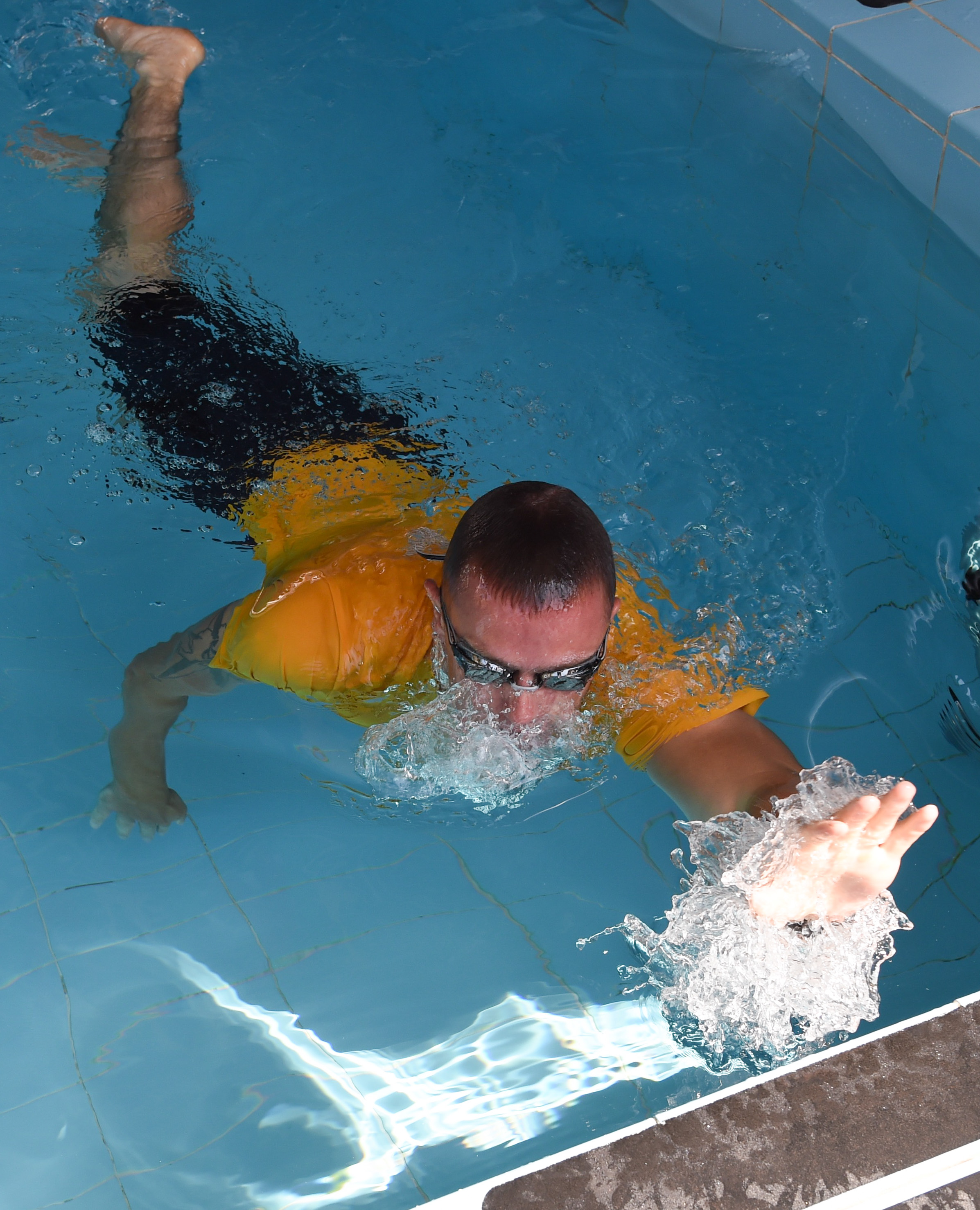 U.S. Navy Petty Officer 2nd Class Adam Agosti, Combined Joint Task Force-Horn of Africa Seabees, reaches for the wall during the 240-meter Navy swim test for the Joint Warrior Competition, Nov. 19, 2016, Camp Lemonnier, Djibouti. The swim test occurred after the joint physical fitness test and the joint combat fitness test. These two events were comprised of pull-ups, push-ups, sit-ups, two-mile run, five-mile ruck march, a low crawl, tourniquet application, buddy carry, radio medical evacuation, grenade toss, tire flip, ammo can carry, dead lift, and rope climb. (U.S. Air National Guard photo by Staff Sgt. Penny Snoozy)