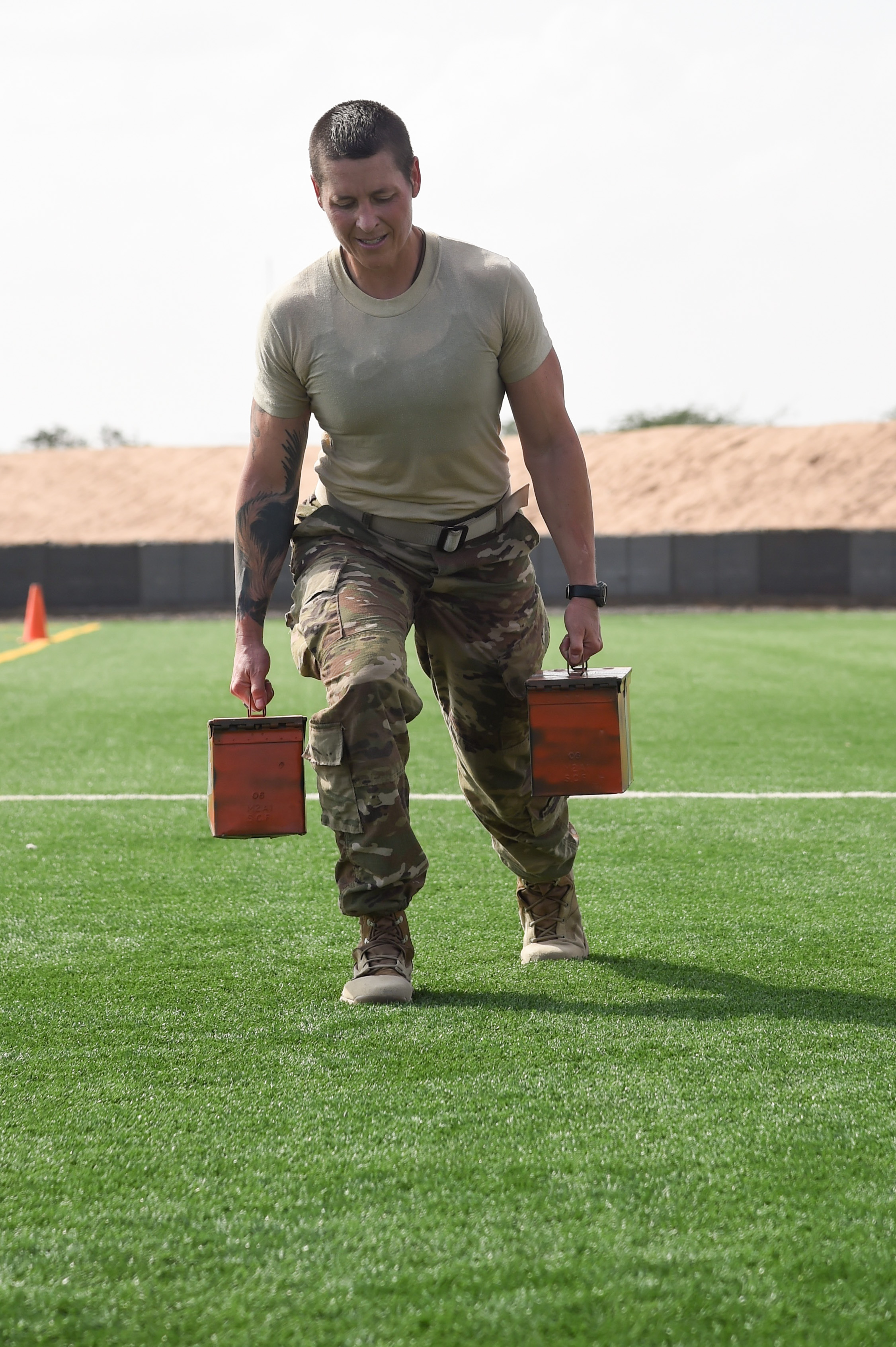 U.S. Army Staff Sgt. Hannah Mabel, Combined Joint Task Force-Horn of Africa, lunges 50 meters with ammo cans during the Joint Warrior Competition, Nov. 19, 2016, Camp Lemonnier, Djibouti. After the joint physical fitness test, participants started the joint combat fitness test. The combat test was comprised of a low crawl, tourniquet application, buddy carry, radio medical evacuation, grenade toss, tire flip, ammo can carry, dead lift, and rope climb. (U.S. Air National Guard photo by Staff Sgt. Penny Snoozy)