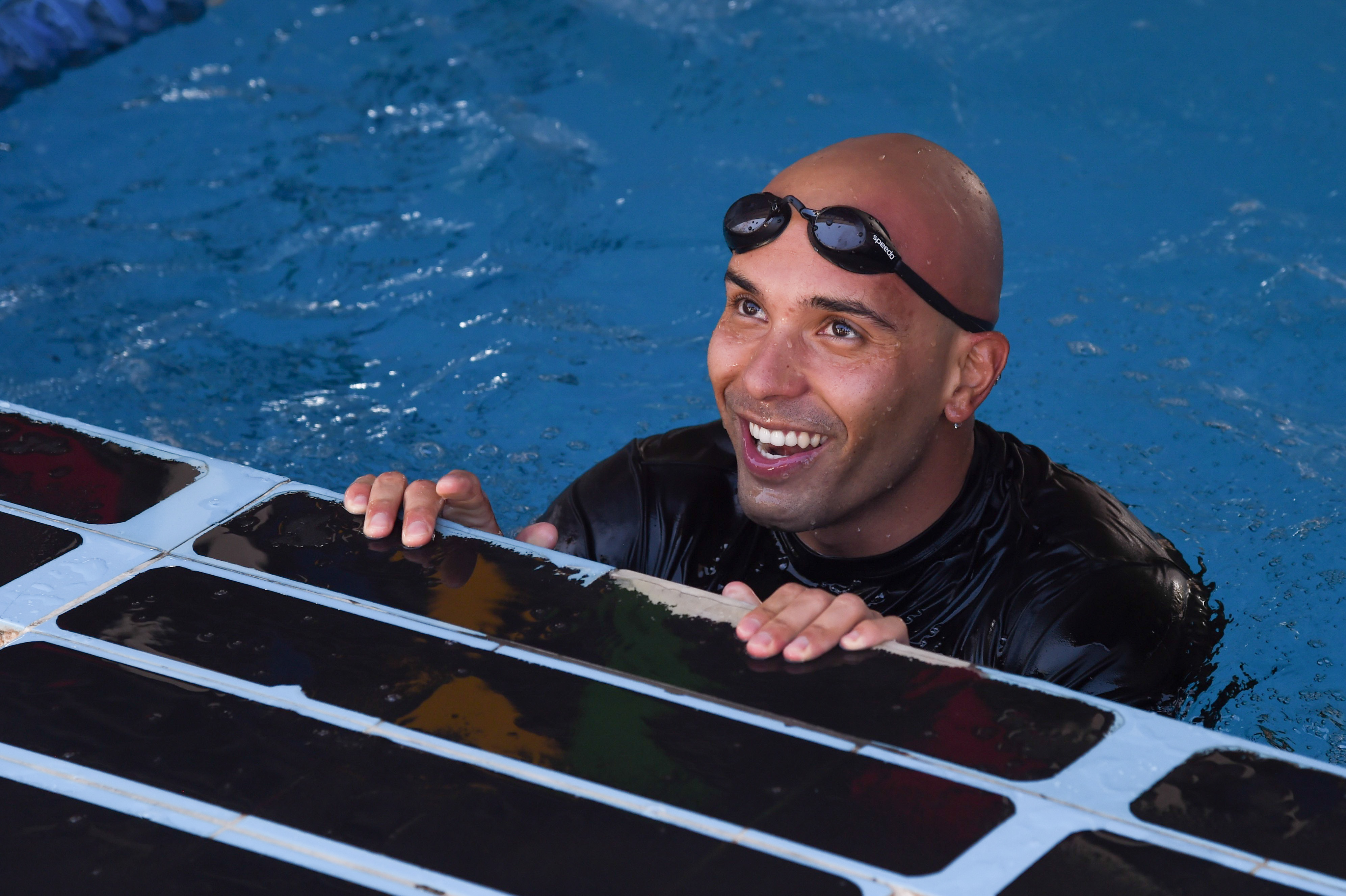 U.S. Army Staff Sgt. Juan Grisales, Combined Joint Task Force-Horn of Africa, completes the 240-meter Navy swim test during the Joint Warrior Competition, Nov. 19, 2016, Camp Lemonnier, Djibouti. The swim test occurred after the joint physical fitness test and the joint combat fitness test. These two events were comprised of pull-ups, push-ups, sit-ups, two-mile run, five-mile ruck march, a low crawl, tourniquet application, buddy carry, radio medical evacuation, grenade toss, tire flip, ammo can carry, dead lift, and rope climb. (U.S. Air National Guard photo by Staff Sgt. Penny Snoozy)