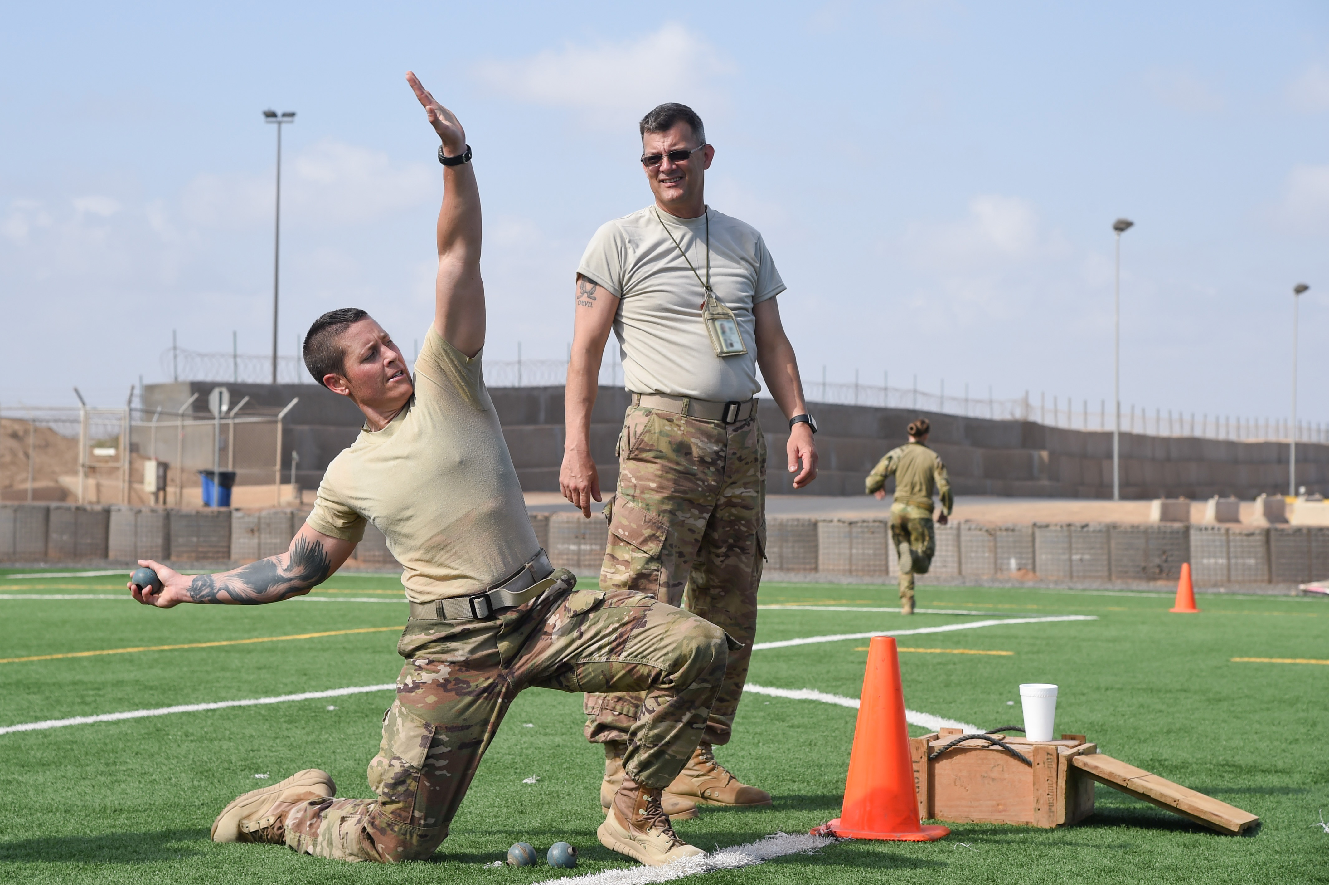 U.S. Army Staff Sgt. Hannah Mabel, Combined Joint Task Force-Horn of Africa, takes part in a grenade toss during the Joint Warrior Competition, Nov. 19, 2016, Camp Lemonnier, Djibouti. After the joint physical fitness test, participants started the joint combat fitness test. The combat test was comprised of a low crawl, tourniquet application, buddy carry, radio medical evacuation, grenade toss, tire flip, ammo can carry, dead lift, and rope climb. (U.S. Air National Guard photo by Staff Sgt. Penny Snoozy) (Portions of image blurred for security)