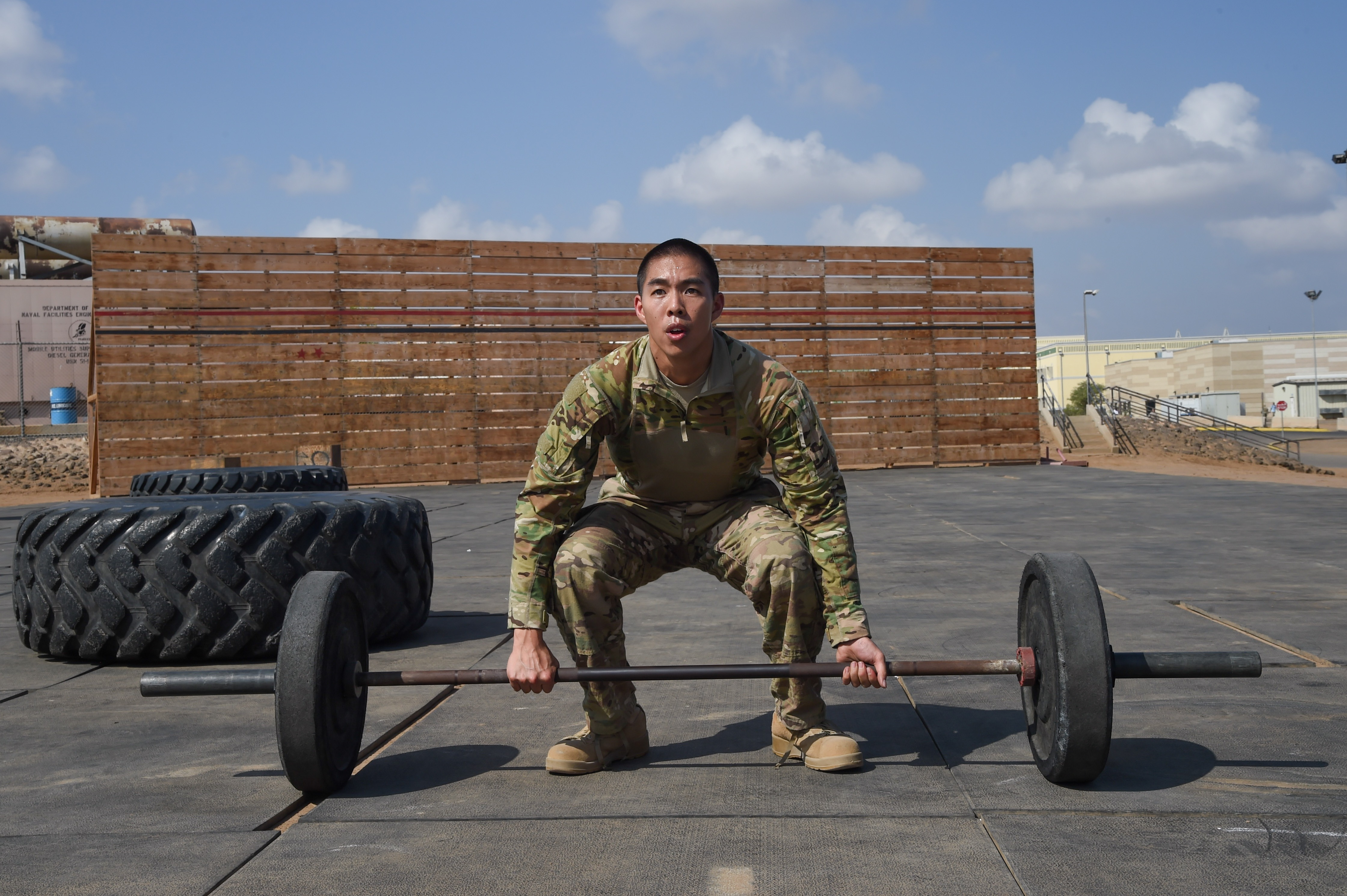 U.S. Air Force Cpt. Alexander Leong, Combined Joint Task Force-Horn of Africa personnel specialist, prepares for fifteen repetitions of a 135-pound deadlift during the Joint Warrior Competition, Nov. 19, 2016, Camp Lemonnier, Djibouti. After the joint physical fitness test, participants started the joint combat fitness test. The combat test was comprised of a low crawl, tourniquet application, buddy carry, radio medical evacuation, grenade toss, tire flip, ammo can carry, dead lift, and rope climb. (U.S. Air National Guard photo by Staff Sgt. Penny Snoozy)