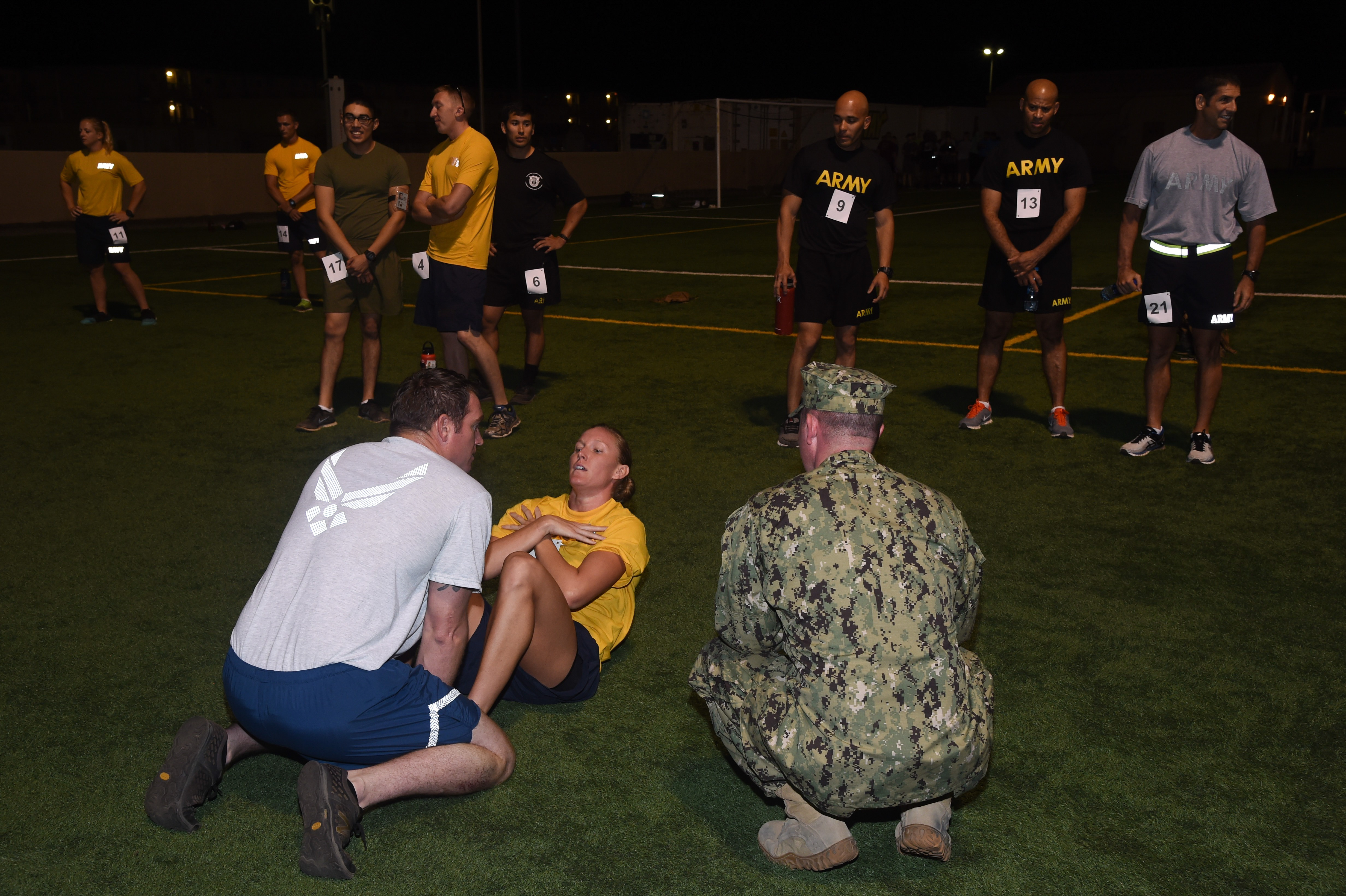 U.S. service members assigned to Combined Joint Task Force-Horn of Africa and Camp Lemonnier participate in the Joint Warrior Competition, Nov. 19, 2016, Camp Lemonnier, Djibouti. The third portion of the joint physical fitness test was the Navy curl-up. Members involved in the event met on the turf field pre-dawn to begin the day of events. (U.S. Air National Guard photo by Staff Sgt. Penny Snoozy)