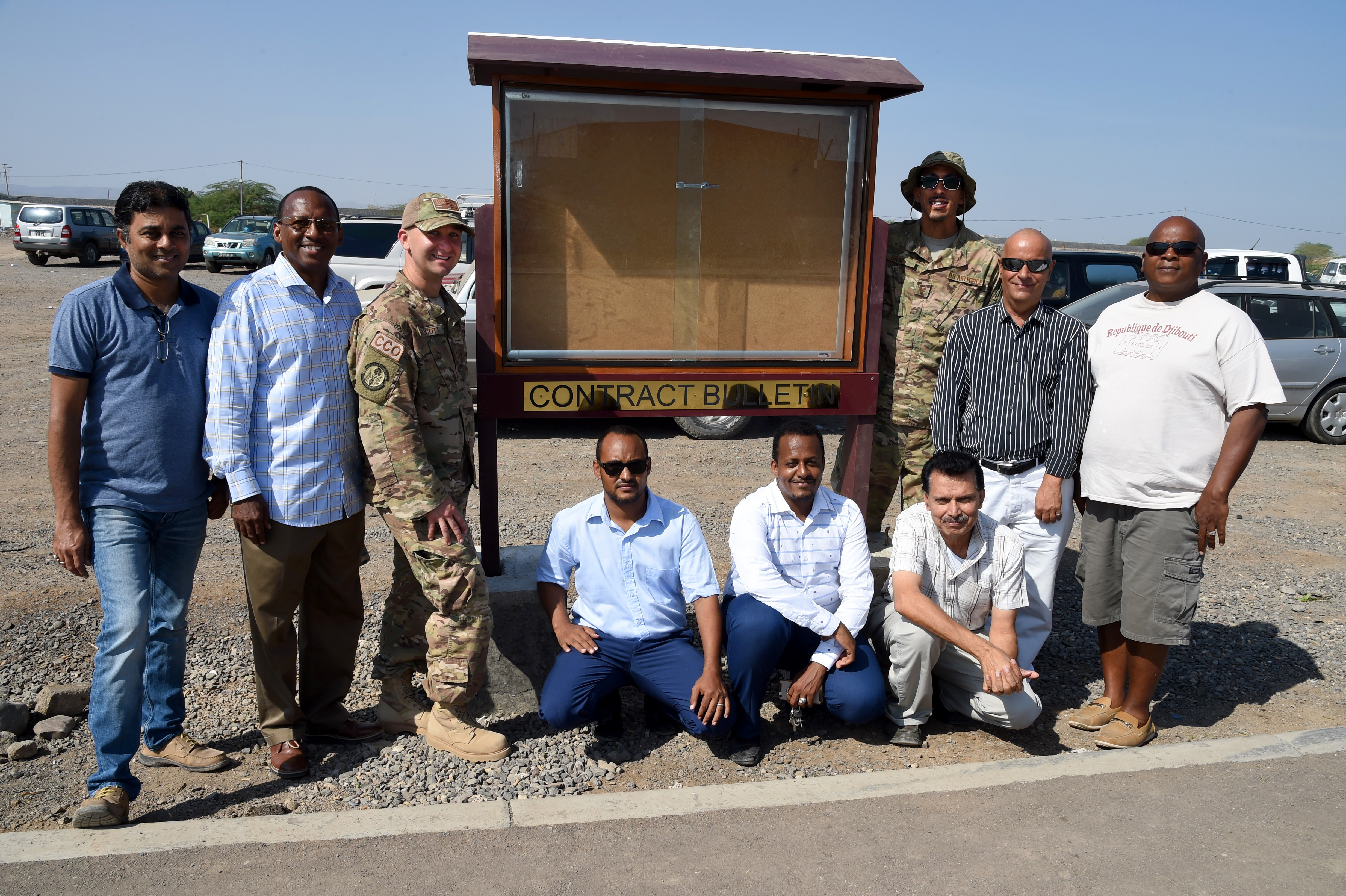 "U.S. Air Force Combined Joint Task Force-Horn of Africa contingency contracting officers, 726th Expeditionary Air Base Squadron, pose with Camp Lemonnier contractors for a photo next to the new contracting bulletin board, Dec. 6, 2016, in Djibouti, Djibouti. The contract bulletin board is posted in a gathering area of the local community and provides Djiboutian businesses with easier access to information and contacts for contracting opportunities. This project aligns with the ""Djiboutian First"" legislation, which supports the economy of Djibouti by providing qualified businesses with contractual preference. (U.S. Air National Guard photo by Staff Sgt. Penny Snoozy)"