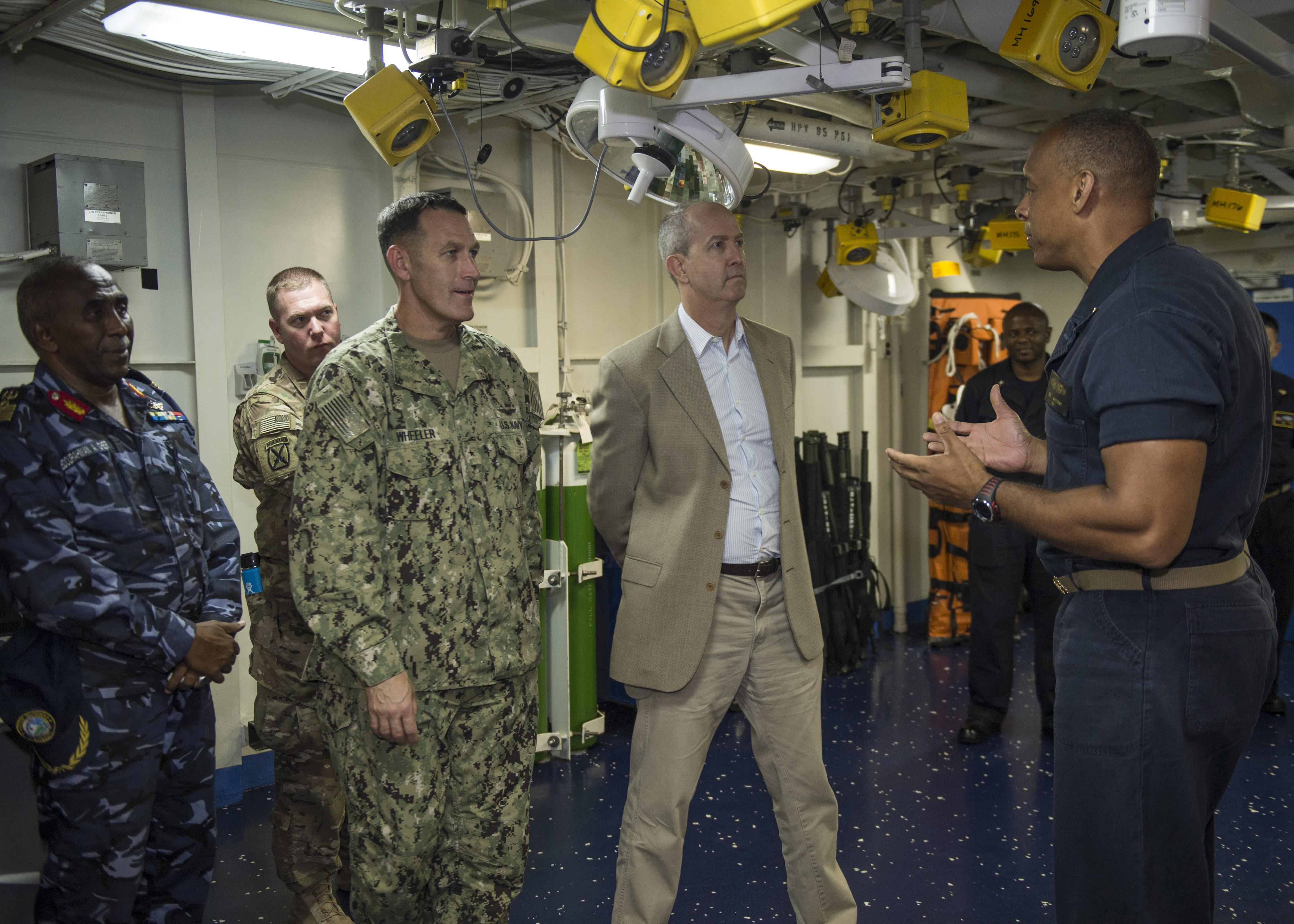 GULF OF ADEN (Dec. 16, 2016) USS Makin Island (LHD 8) Senior Medical Officer, Cmdr. Karlwin Matthews, right, speaks with Chief of Djiboutian Navy Col. Abdourahman Cher, left, Rear Adm. William W. Wheeler, Deputy Commander, Combined Joint Task Force – Horn of Africa, and the U.S. Ambassador to Djibouti, Mr. Tom Kelly in the ship's medical triage. Makin Island is deployed as part of the Makin Island Amphibious Ready group to the U.S. 5th Fleet area of operations to support maritime security operations and theater security cooperation efforts. (U.S. Navy photo by Petty Officer 3rd Class Devin M. Langer)