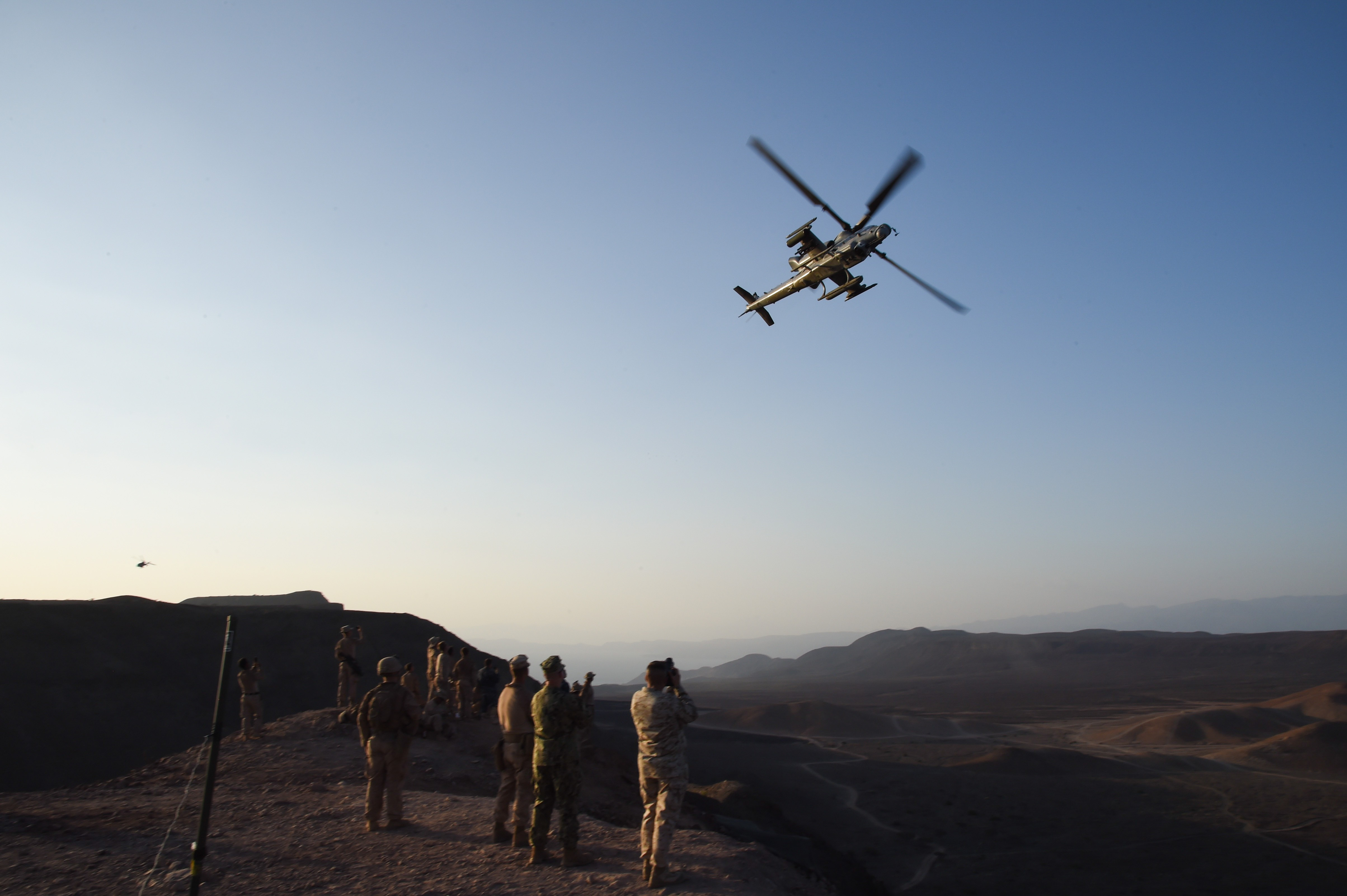 U.S. Marine Corps members with the11th Marine Expeditionary Unit (MEU), and Sailors from the Makin Island Amphibious Ready Group, watch a Super Cobra attack helicopter fly over after a helo-borne raid on the range during Exercise Alligator Dagger, Dec. 18, 2016, at Arta Plage, Djibouti. The exercise allows opportunities for the 11th MEU to maintain their respective skills and proficiencies while intermittently participating in bilateral training with the French. (U.S. Air National Guard photo by Staff Sgt. Penny Snoozy)