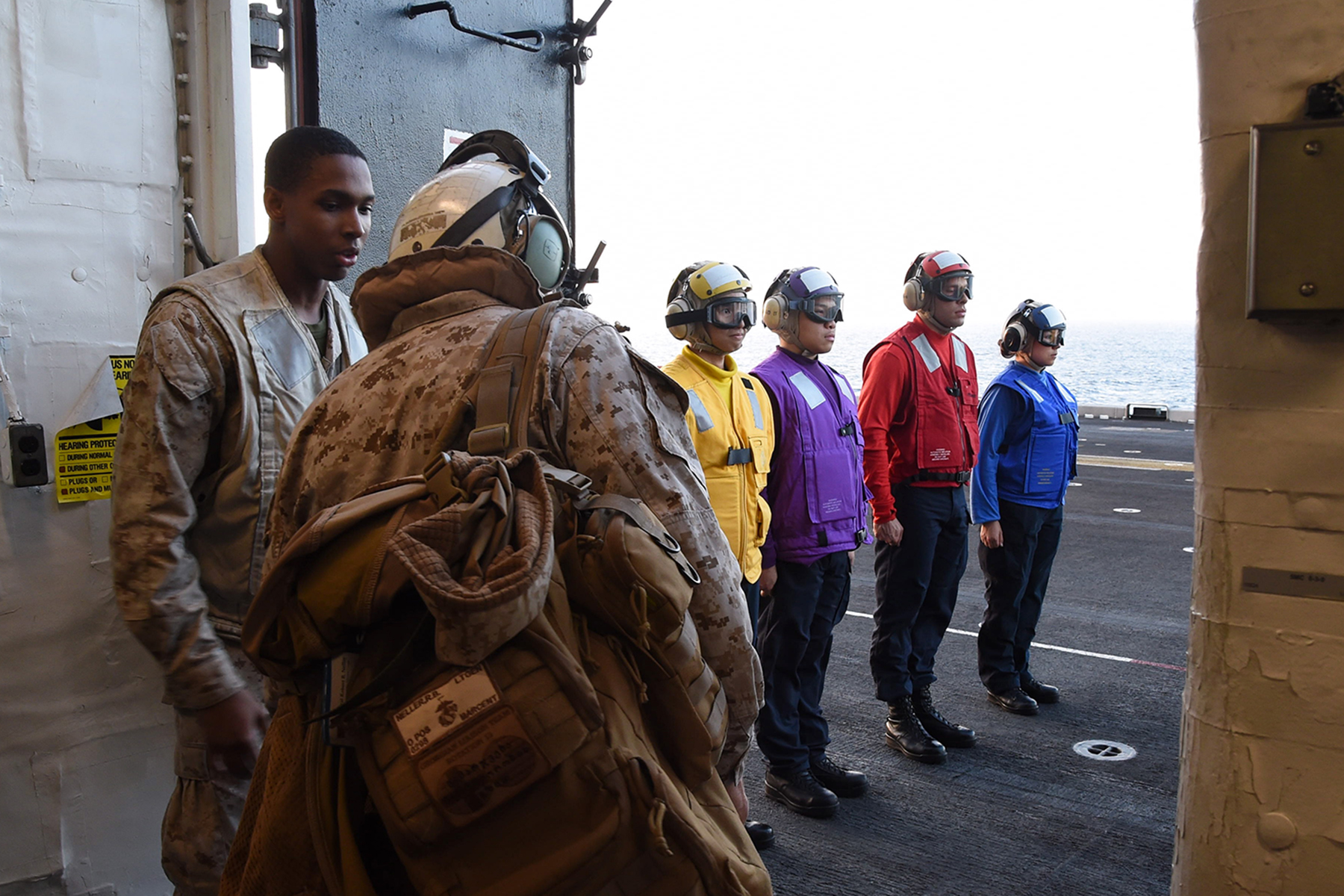 U.S. Marine Corps Gen. Robert B. Neller, 37th Commandant of the Marine Corps, prepares to depart from the flight deck of the amphibious assault ship USS Makin Island (LHD 8), in the Gulf of Aden, Dec. 23, 2016. Sailors involved in flight deck operations wear color-coded apparel that identifies their specialization. (U.S. Air National Guard photo by Staff Sgt. Penny Snoozy)