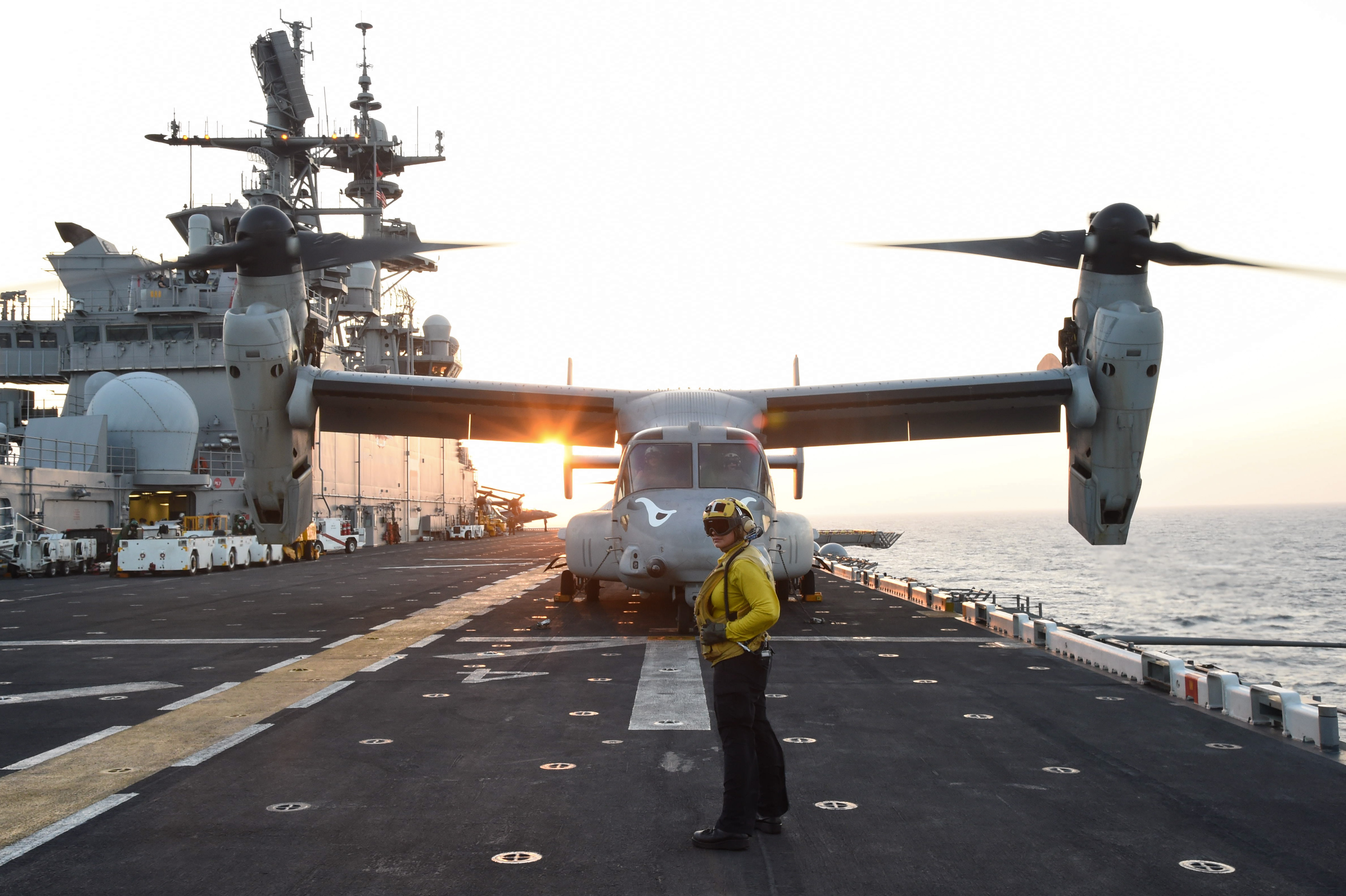 A U.S. Navy Sailor, assigned to the USS Makin Island (LHD 8), prepares to launch an MV-22 Osprey transporting the Commandant of the Marine Corps from the flight deck of the amphibious assault ship Makin Island to Camp Lemonnier, in the Gulf of Aden, Dec. 23, 2016. Sailors involved in flight deck operations wear color-coded apparel that identifies their specialization. (U.S. Air National Guard photo by Staff Sgt. Penny Snoozy)