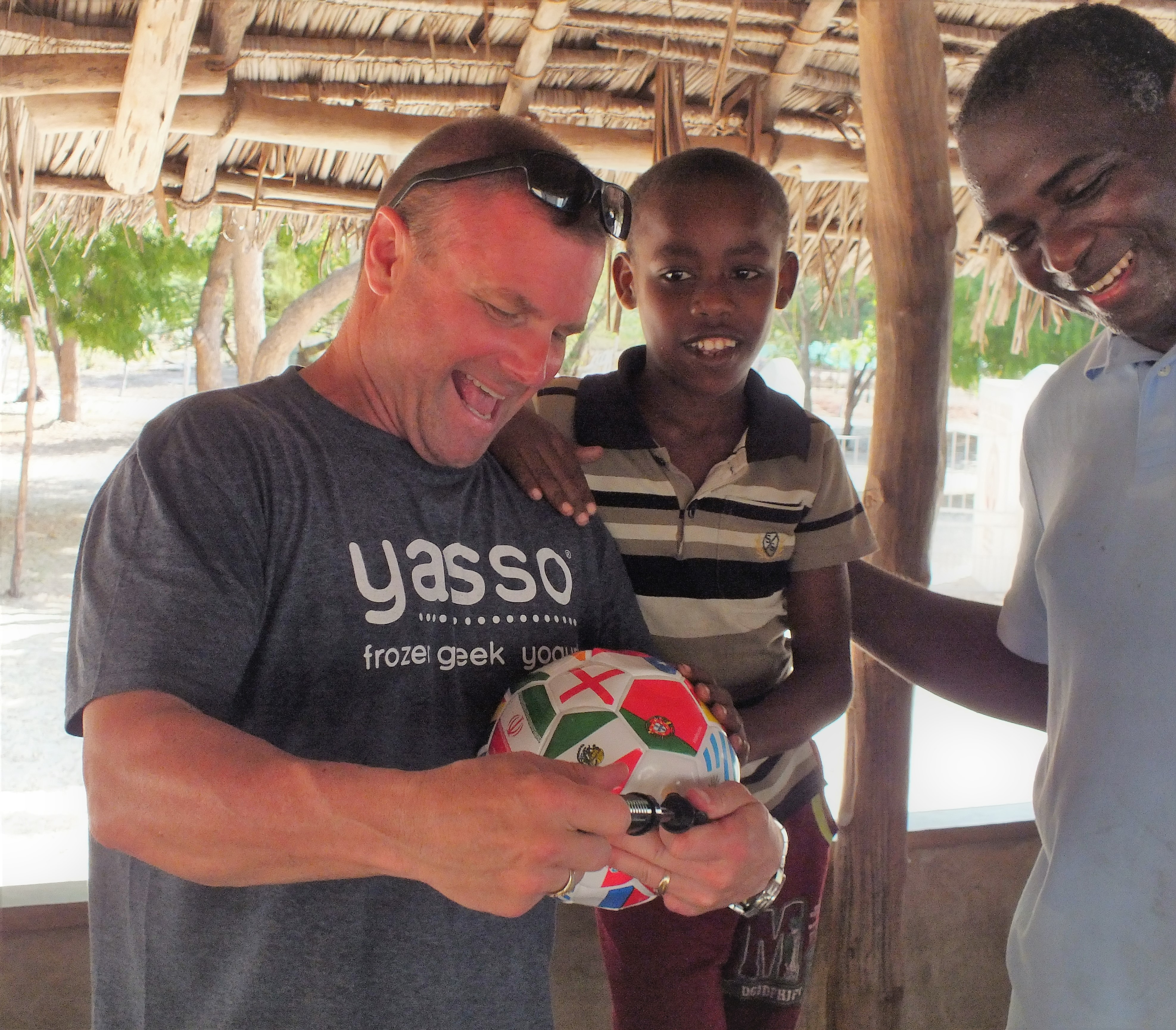 U.S. Army Chaplain (CPT) Donald A. Mooney, Combined Joint Task Force-Horn of Africa (CJTF-HOA) Religious Affairs, and U.S. Navy Petty Officer 1st Class Joseph Pendantonga, Chaplain's Assistant, CJTF-HOA Religious Affairs, pump up a soccer ball to distribute at the Anidan Children's House in Lamu, Kenya Dec. 23, 2016. U.S. Navy Seabees and CJTF-HOA Religious Affairs personnel are assigned to Kenya to assist with repairs and construction efforts at the Anidan Children's Home. (Courtesy Photo)