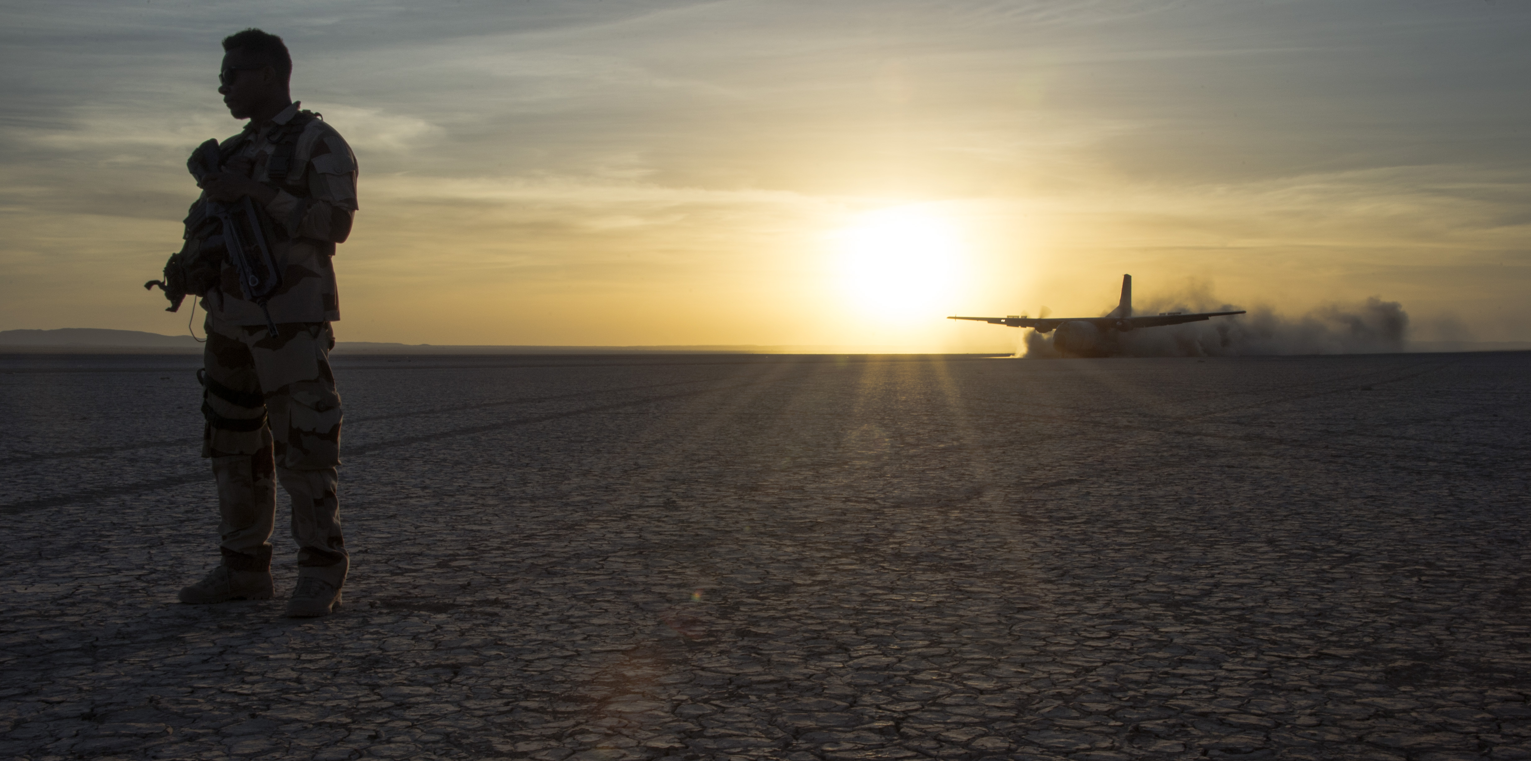 A French military member keeps onlookers at a safe distance from the landing area as a French C-160 Transall transport aircraft touches down on the rough terrain during the French live fire demonstration near Grand Bara, Djibouti, Jan. 14, 2017. The C-160 Transall is a tactical transport aircraft capable of carrying up to 93 troops with the ability to land on an airstrip as short as 400 meters. (U.S. Air National Guard photo by:  Staff Sgt. Christian Jadot)