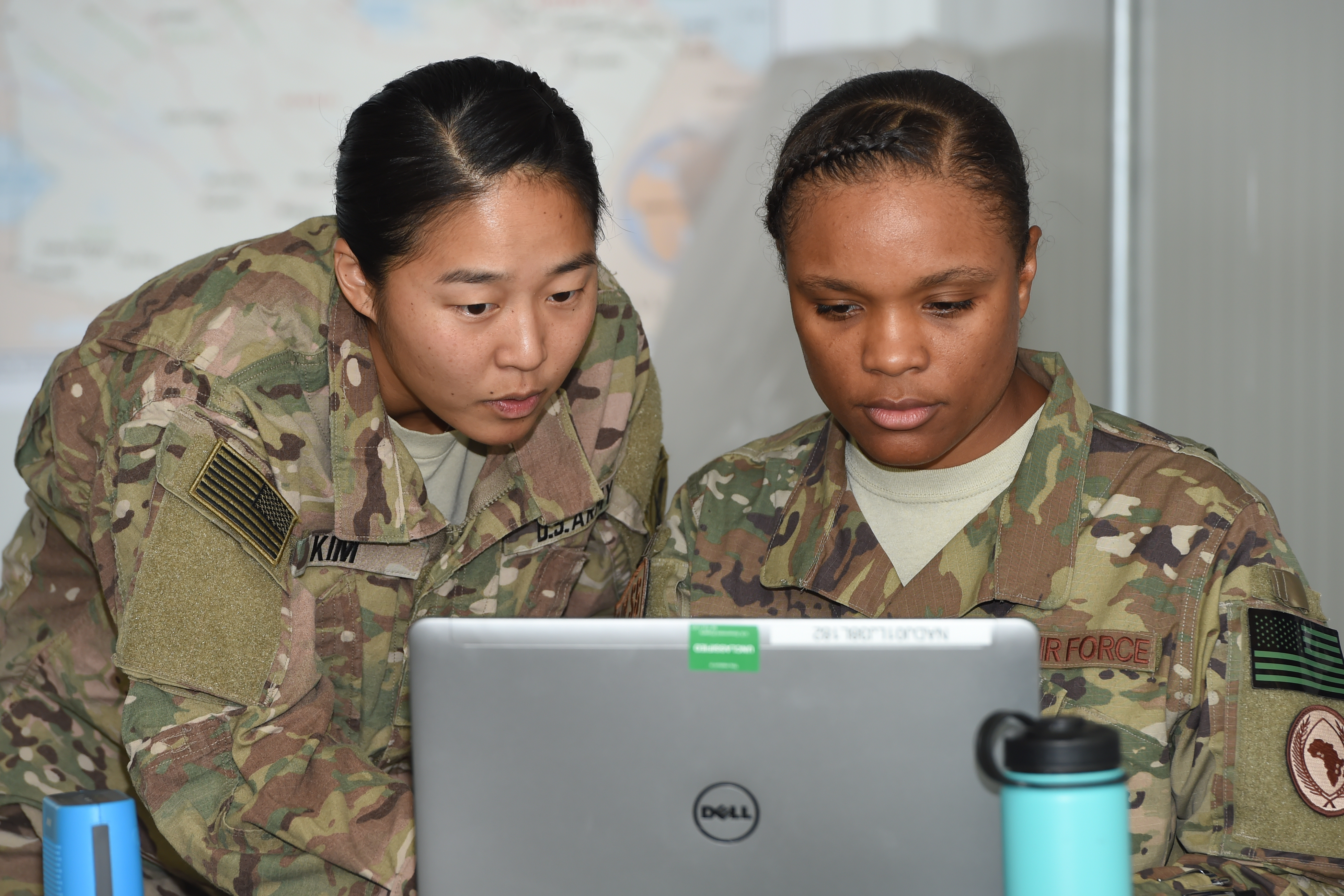 U.S. Army 1st Lt. Elizabeth Kim, officer in charge of environmental health for Camp Lemonnier, confers with U.S. Air Force Tech. Sgt. Pauline Jones, noncommissioned officer in charge of preventative medicine, during a Field Sanitation Team Training course at Camp Lemonnier, Djibouti, Feb. 14, 2017. As course instructors, Kim and Jones taught participating service members field sanitation practices proven to mitigate disease and non-battle related injuries. (U.S. Air National Guard photo by Master Sgt. Paul Gorman)