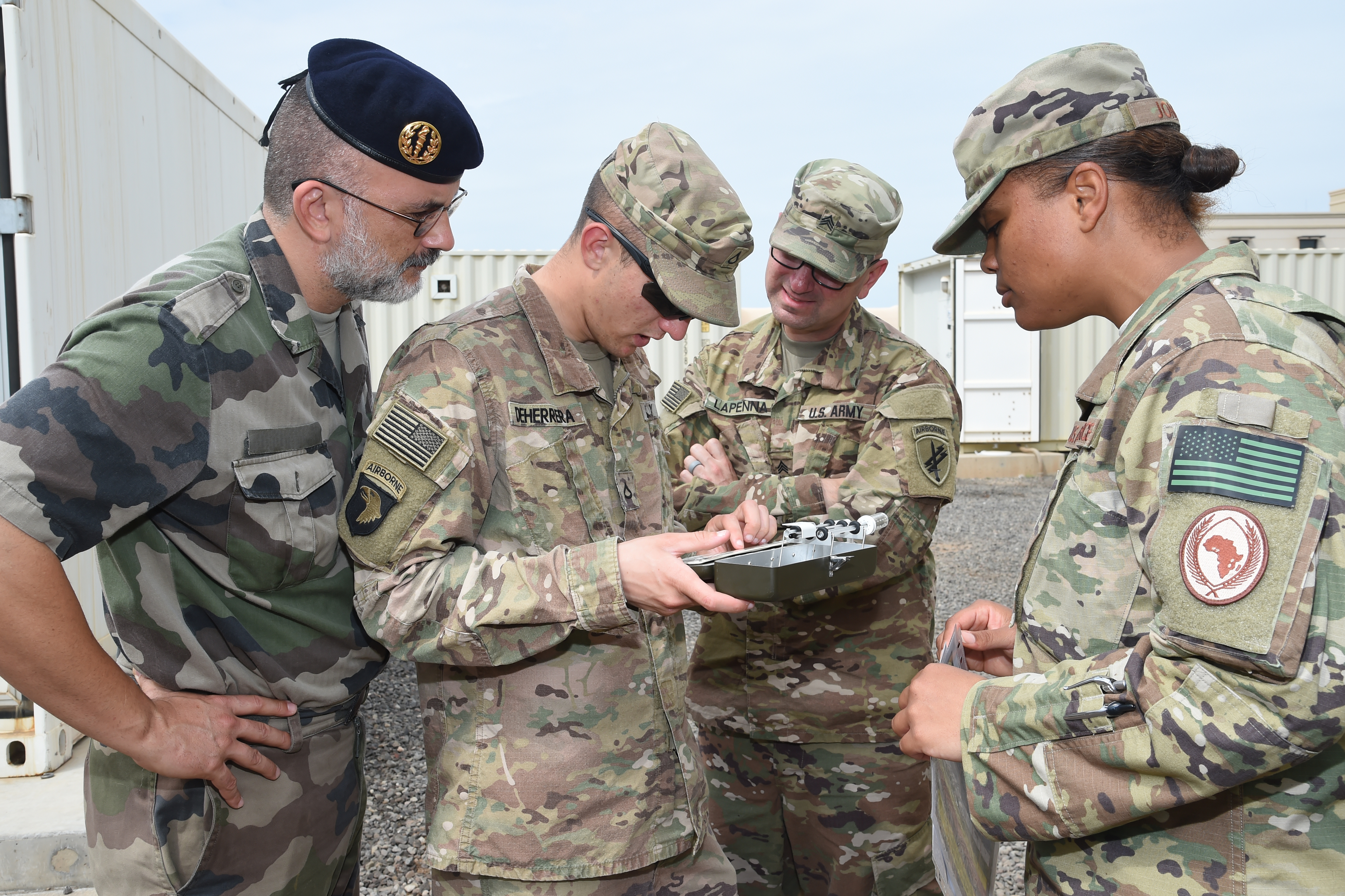U.S. and French military members demonstrate their ability to use a wet bulb-globe temperature (WBGT) kit during a Field Sanitation Team Training course at Camp Lemonnier, Djibouti, Feb. 14, 2017. The WBGT kit is an instrument for providing information on hot weather risks to the health of troops undergoing training. (U.S. Air National Guard photo by Master Sgt. Paul Gorman) (Foreign service members name tape has been obscured for OPSEC)