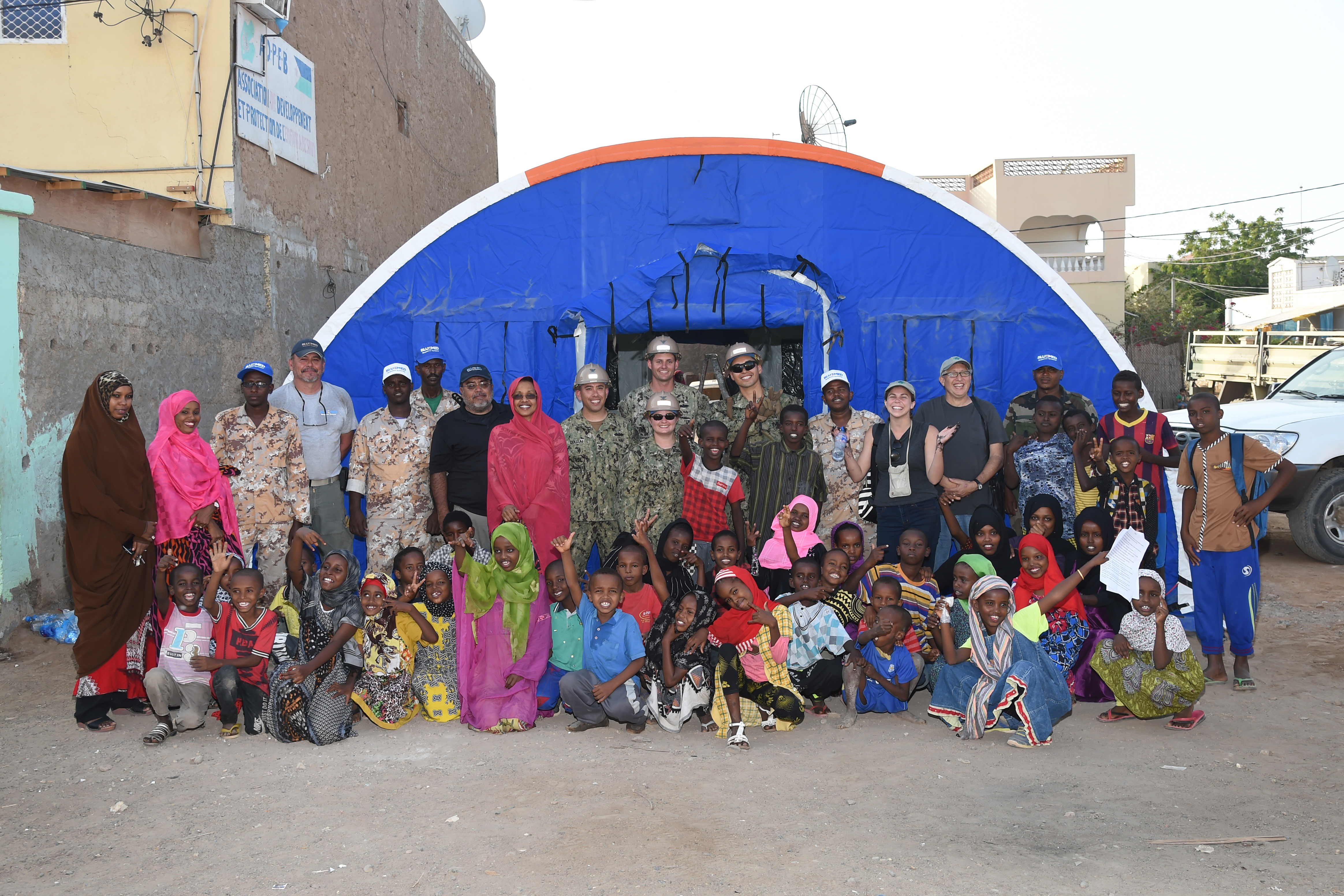 U.S. Navy Seabees with Naval Mobile Construction Battalion 1, join Djibouti Armed Forces soldiers, and representatives from Alaska Shelters, the Global Action Coalition, the Association for the Development and Protection of Children (ADPEB) and local youth following the construction of a modular shelter system in Djibouti City, Feb. 27, 2017. The shelter is one of six donated by Alaska Shelters through the Global Action Coalition, and will give the ADPEB additional shelter and classroom space for homeless children in Djibouti. (U.S. Air National Guard photo by Master Sgt. Paul Gorman)