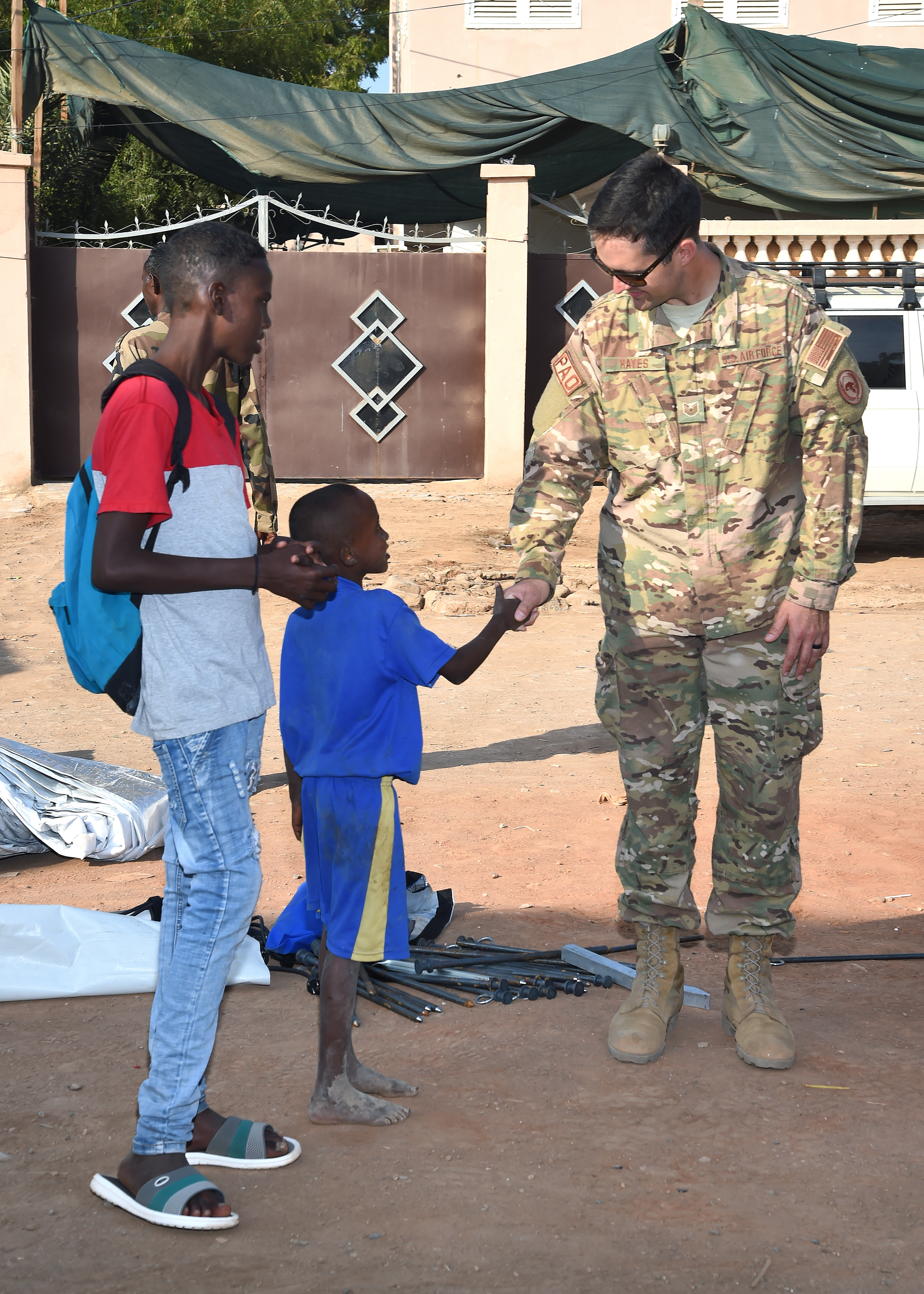 U.S. Air Force Tech. Sgt. Benjamin Hayes, broadcast journalist with Combined Joint Task Force-Horn of Africa, greets children observing the construction of a modular shelter system by U.S. Navy and Djibouti Armed Forces personnel in downtown Djibouti, Feb. 27, 2017. The shelter was one of six donated by U.S. manufacturer Alaska Shelters through the Global Action Coalition, and will provide additional classroom space to the Association for the Development and Protection of Children in downtown Djibouti. (U.S. Air National Guard photo by Master Sgt. Paul Gorman)