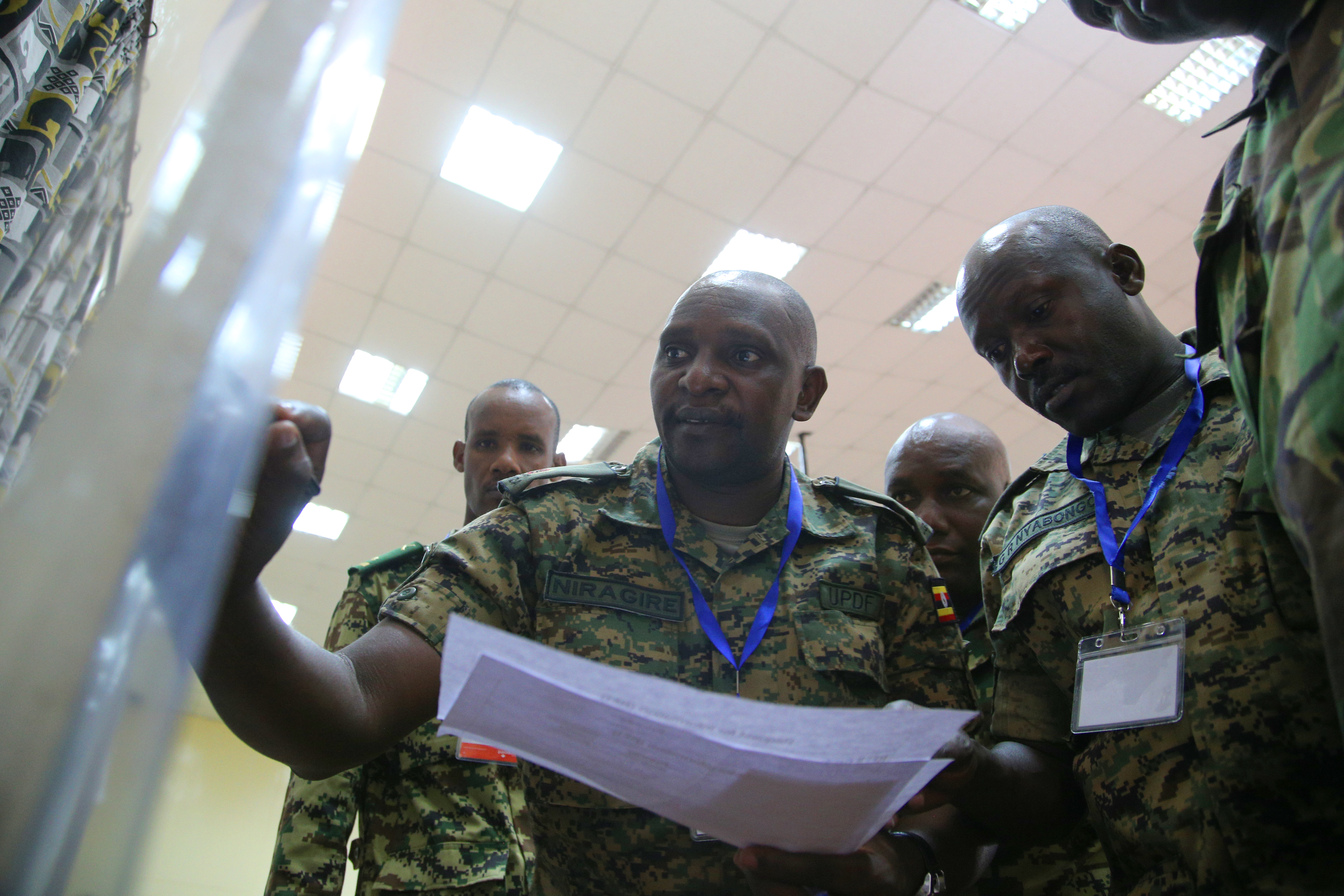 Uganda People's Defense Force (UPDF) Maj. Julius Niragire and UPDF Maj. Godfrey Nyabongo plan and prepare Civil-Military Cooperation staff responses to a simulated humanitarian crisis during the command post exercise of the Africa Contingency Operations Training and Assistance force headquarters training program held at the Humanitarian Peace Support School in Nairobi, Kenya, March 9, 2017. The five-week course was facilitated by the U.S. Department of State and is designed to improve Africa's military capabilities by providing selected training necessary for multinational peace support operations. (U.S. Army photo by Capt. Alán Ortiz)