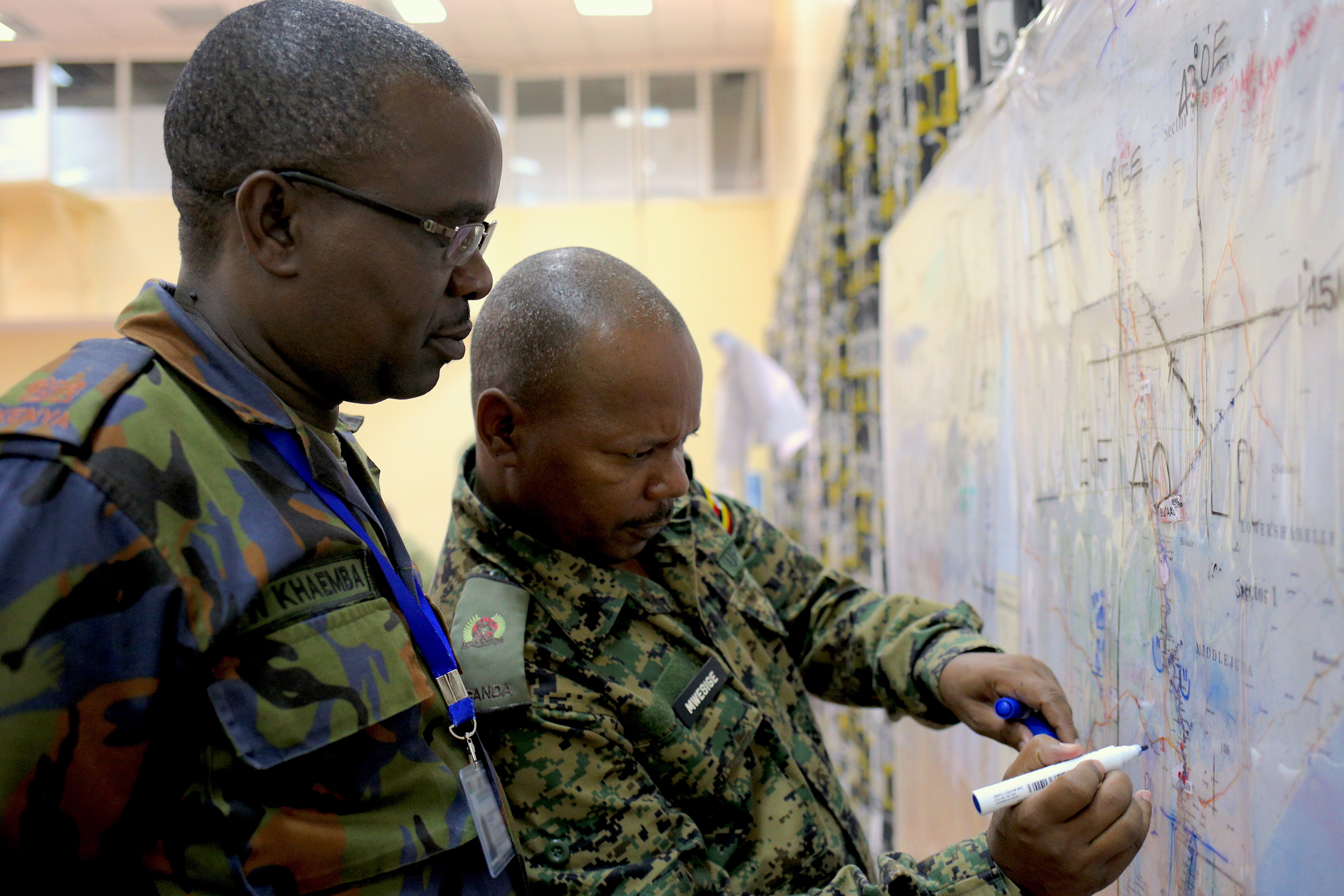 Kenya Defense Force Maj. Andrew Khaema and Uganda People's Defense Force Maj. Patrick Mwesige identify locations designated for relief assistance in response to a simulated humanitarian crisis during the command post exercise of the Africa Contingency Operations Training and Assistance force headquarters training program held at the Humanitarian Peace Support School in Nairobi, Kenya, March 9, 2017. The five-week course was facilitated by the U.S. Department of State and is designed to improve Africa's military capabilities by providing selected training necessary for multinational peace support operations. (U.S. Army photo by Capt. Alán Ortiz)