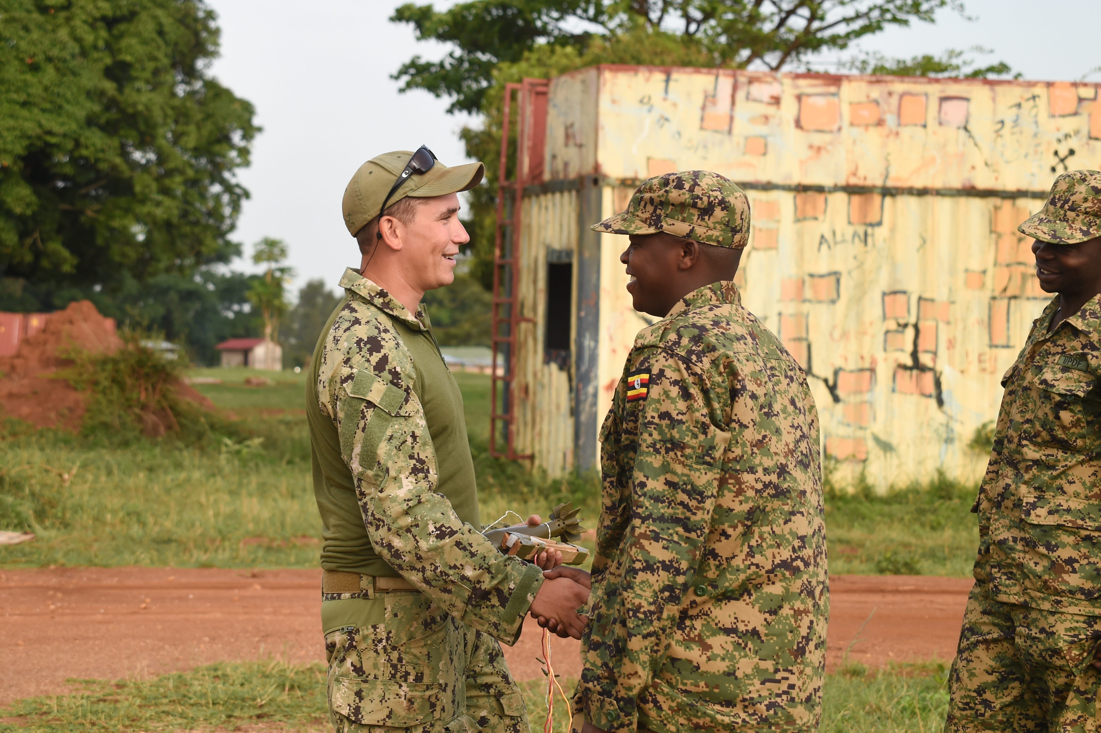 U.S. Navy Explosive Ordnance Disposal Technician 1st Class Dan Steinchen, Combined Joint Task Force-Horn of Africa, Task Force Sparta, EOD Mobile Unit 8, greets a Uganda People's Defense Force (UPDF) member before counter-IED training at Camp Singo, Uganda, March 6, 2017.  The training gave UPDF members a chance to locate and clear IEDs in and around buildings and along the road. (U.S. Air National Guard photo by Staff Sgt. Penny Snoozy)