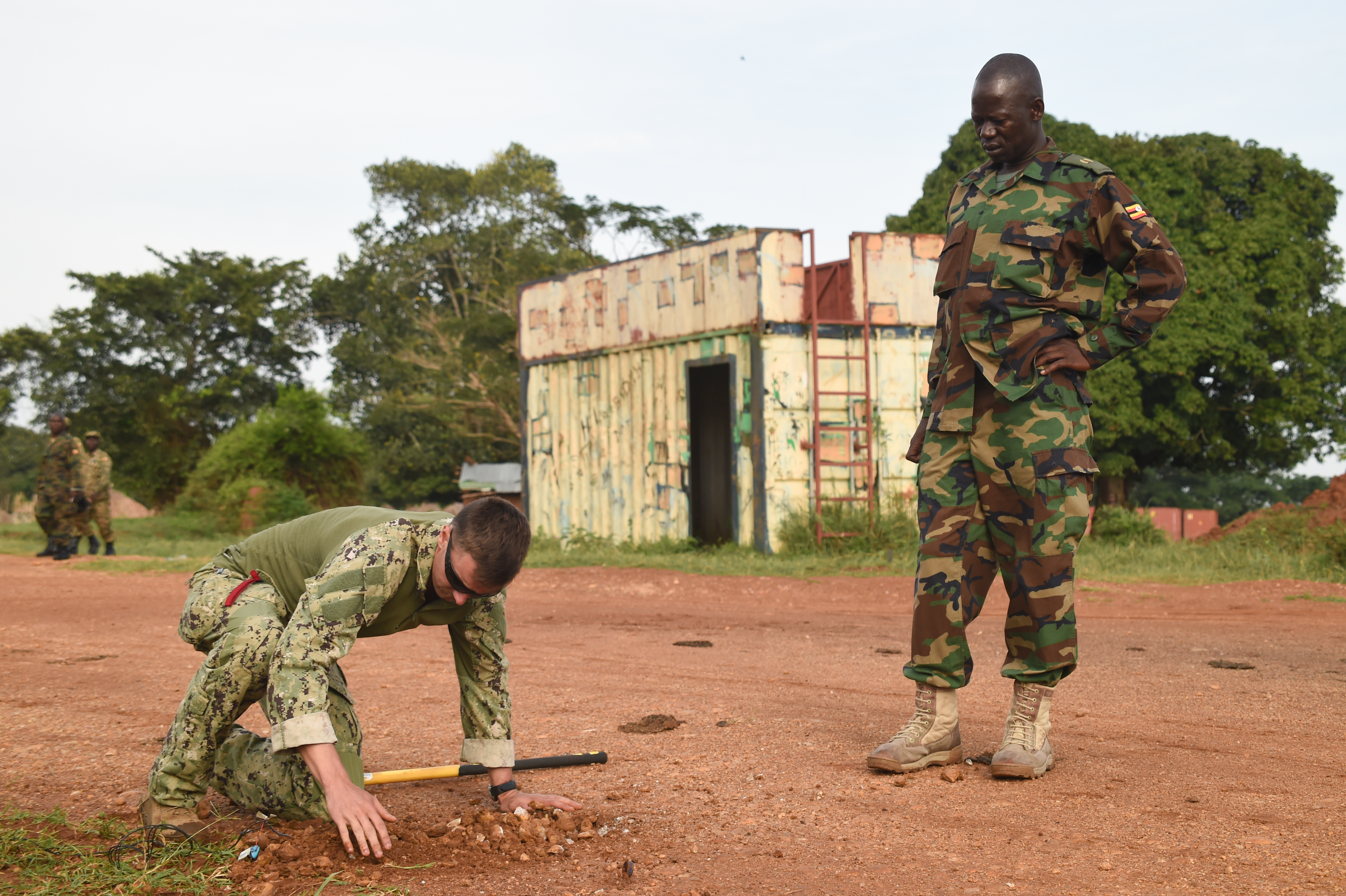 U.S. Navy Explosive Ordnance Disposal Technician 2nd Class Gary Lathrop, Combined Joint Task Force-Horn of Africa, Task Force Sparta, EOD Mobile Unit 8, places a simulated improvised-explosive-device (IED) as a Uganda People's Defense Force (UPDF) cadre observes during counter-IED training at Camp Singo, Uganda, March 6, 2017.  The training gave UPDF members a chance to locate and clear IEDs in and around buildings and along the road. (U.S. Air National Guard photo by Staff Sgt. Penny Snoozy)