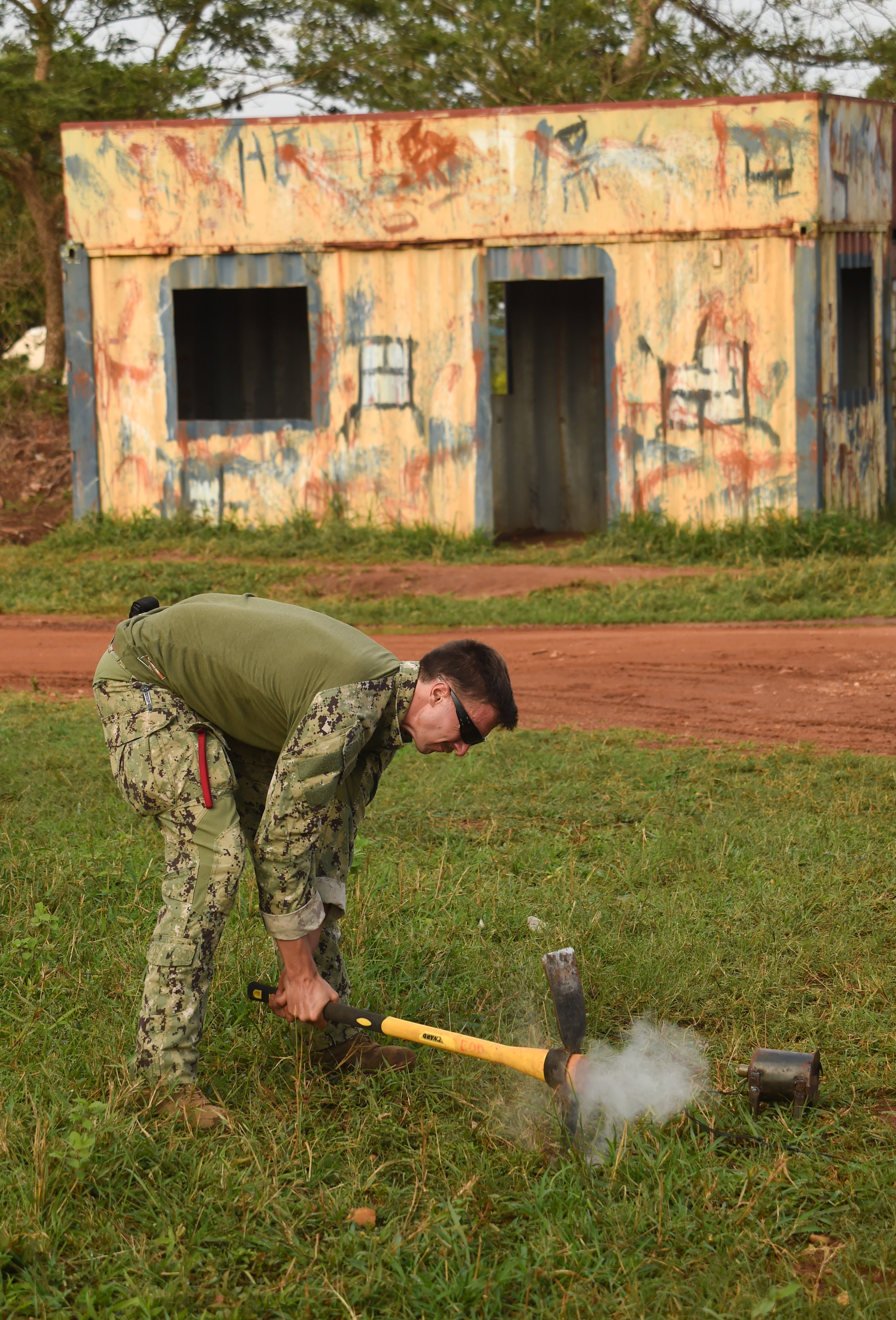 U.S. Navy Explosive Ordnance Disposal Technician 2nd Class Gary Lathrop, Combined Joint Task Force-Horn of Africa, Task Force Sparta, EOD Mobile Unit 8, creates a hole for a simulated improvised-explosive-device (IED) during counter-IED training with Uganda People's Defense Force (UPDF) members at Camp Singo, Uganda, March 6, 2017.  The training gave UPDF members a chance to locate and clear IEDs in and around buildings and along the road. (U.S. Air National Guard photo by Staff Sgt. Penny Snoozy)