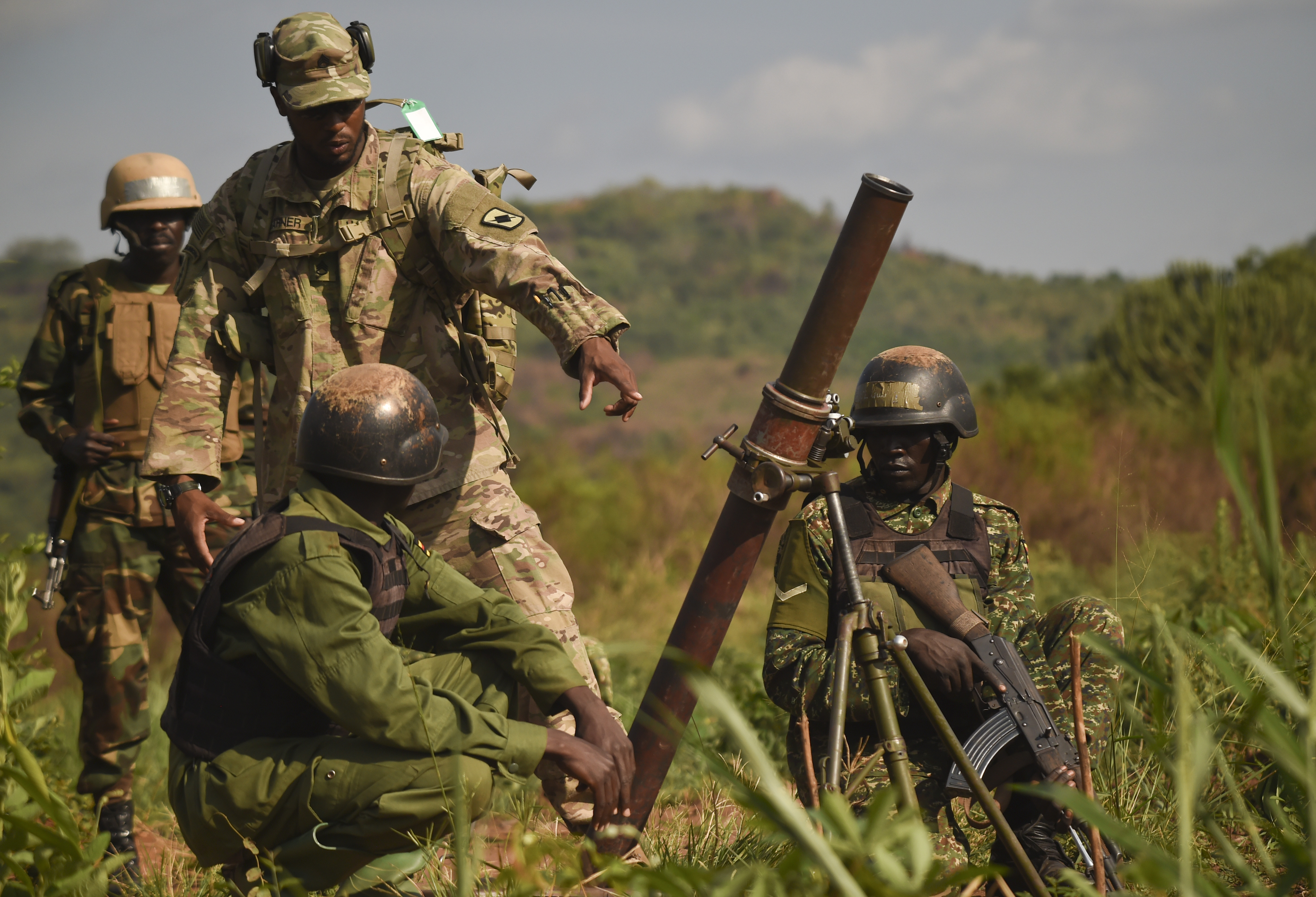 U.S. Army Staff Sgt. John Garner, Combined Joint Task Force-Horn of Africa mortarman subject matter expert, assists Uganda People's Defense Force soldiers, Ugandan Battle Group 22 (UGABAG 22), as they prepare to fire mortars during a live fire exercise at Camp Singo, Uganda, Feb. 27, 2017. The live fire is part of a 12-week pre-deployment training course for UGABAG 22. (U.S. Air National Guard photo by Staff Sgt. Penny Snoozy)